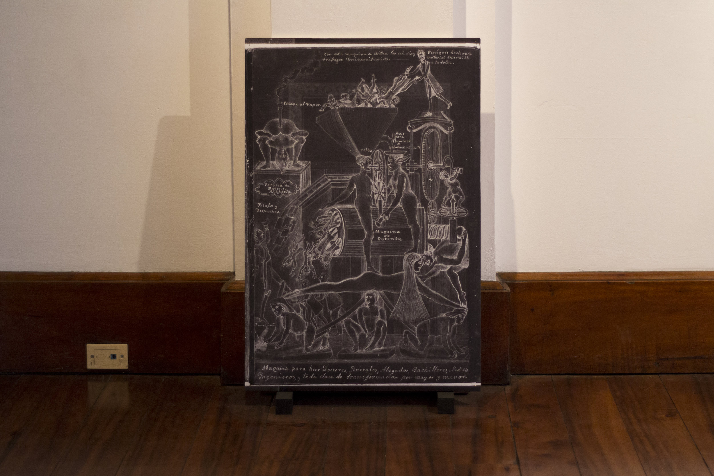 "Image in El cuaderno rojo. Property of Archivo Nacional de Costa Rica. Installation View, Alianza Francesa, Costa Rica.  The top of the image reads: ""With this machine work and university studies are avoided"". Image Verónica Alfaro. 2017"