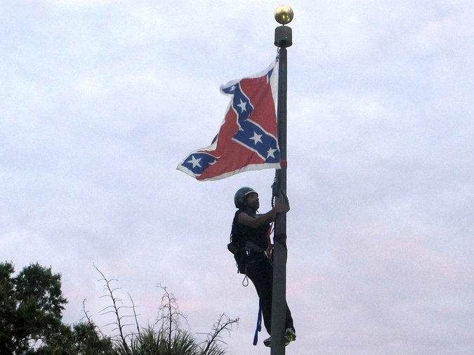 Newsome climbing the flagpole in front of the State House in Charleston.  (Credit: Bruce Smith/Associated Press)