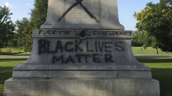 "The ""Black Lives Matter"" graffiti at the monument's base. The events since the police murder of Mike Brown in nearby Ferguson have cast a light on the racist practices of the area's police.  (Credit: Reuters)"