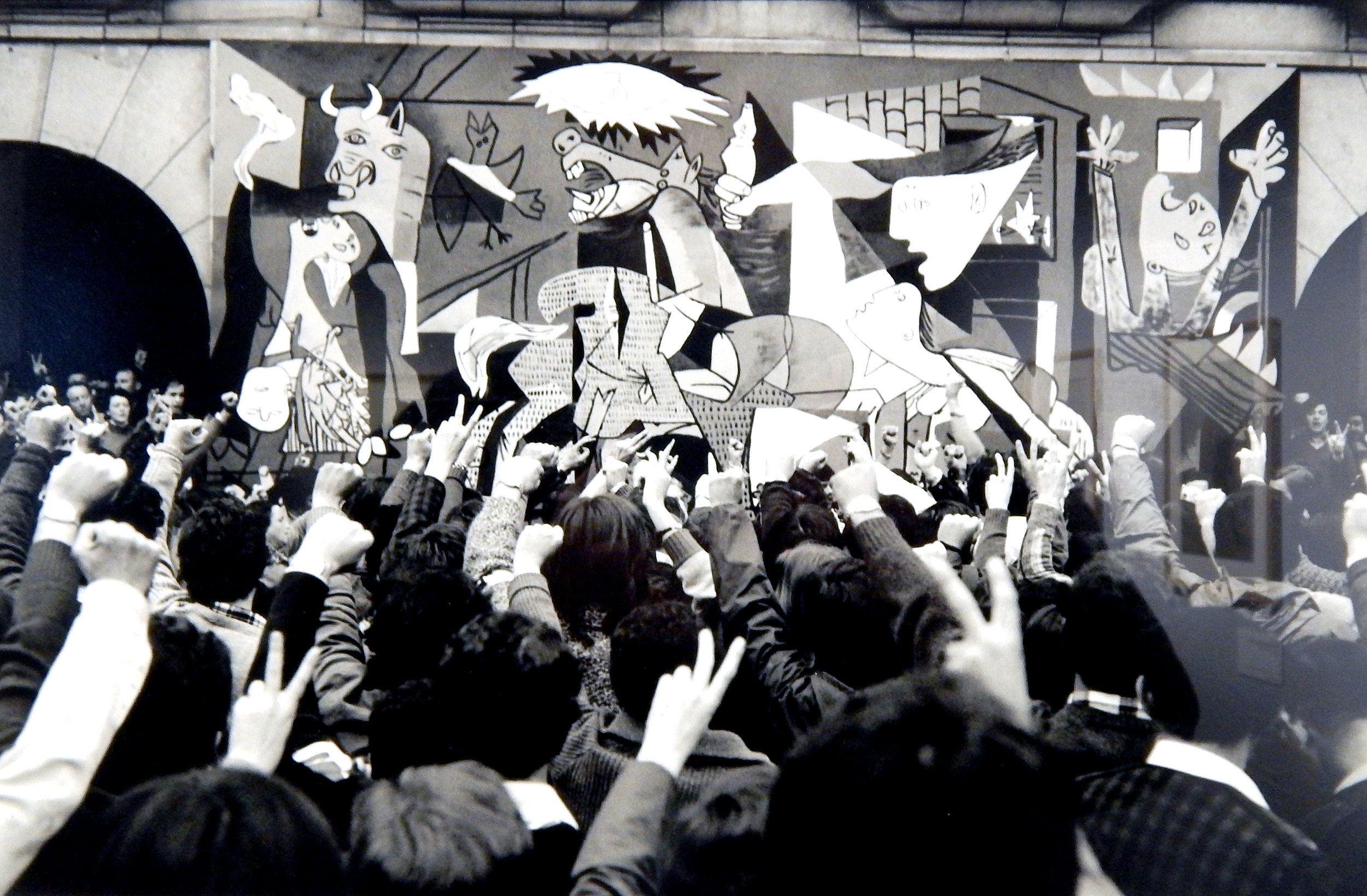 Leonard Freed,  Residents of Guernica in front of a mural replica of Pablo Picasso's painting  (1977)