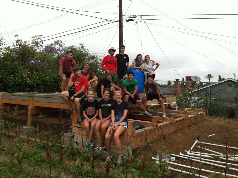 A group of volunteers help construct an aquaponic farm at a University in Los Angeles, CA.