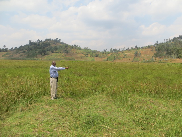 Faustin pointing to his acres of productive land waiting for development!