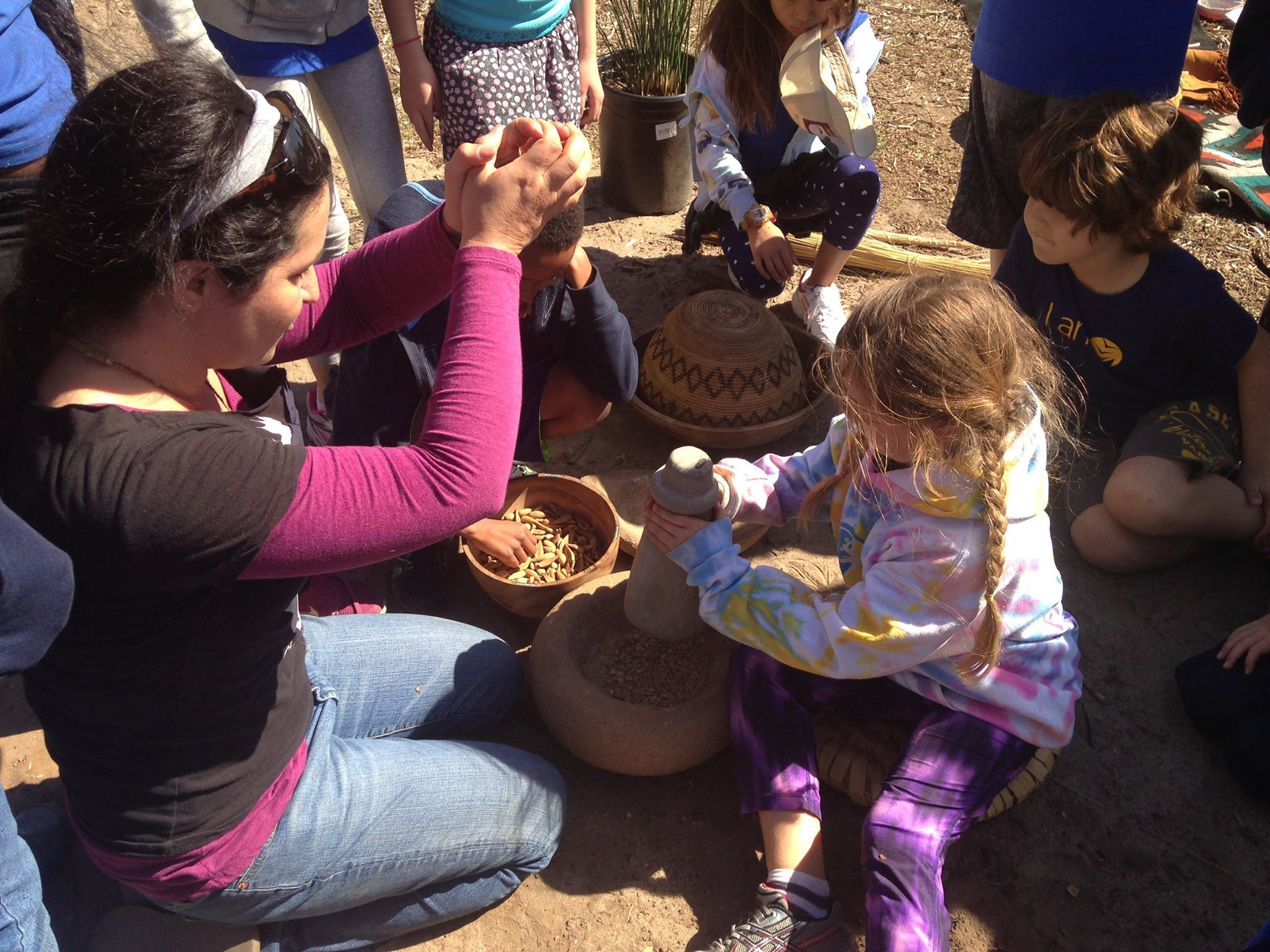 Children excitedly wait their turn to try their hand at crushing acorns to make acorn flour.