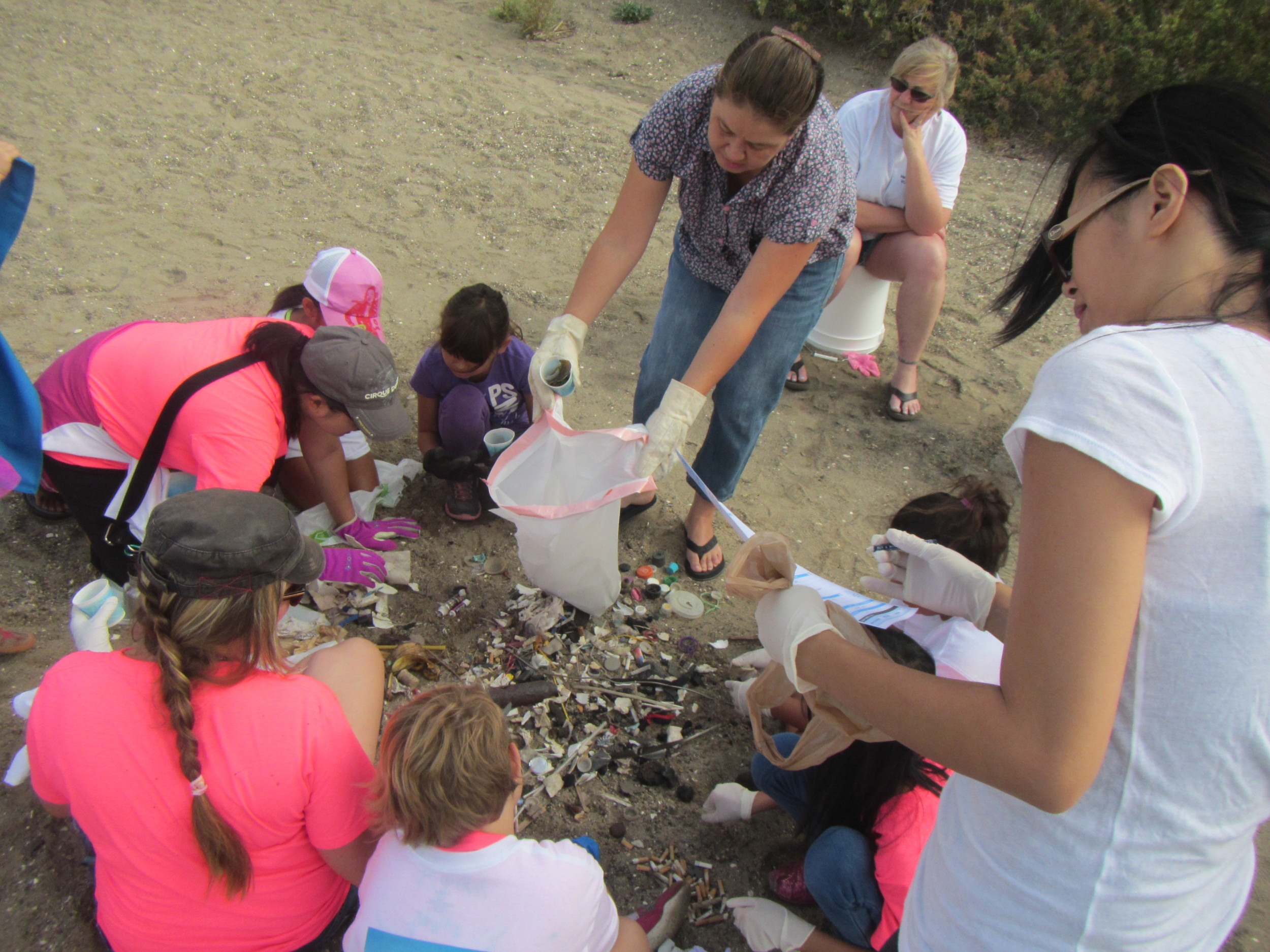 Students participate in a beach clean up and compile the mass to examine and record together.