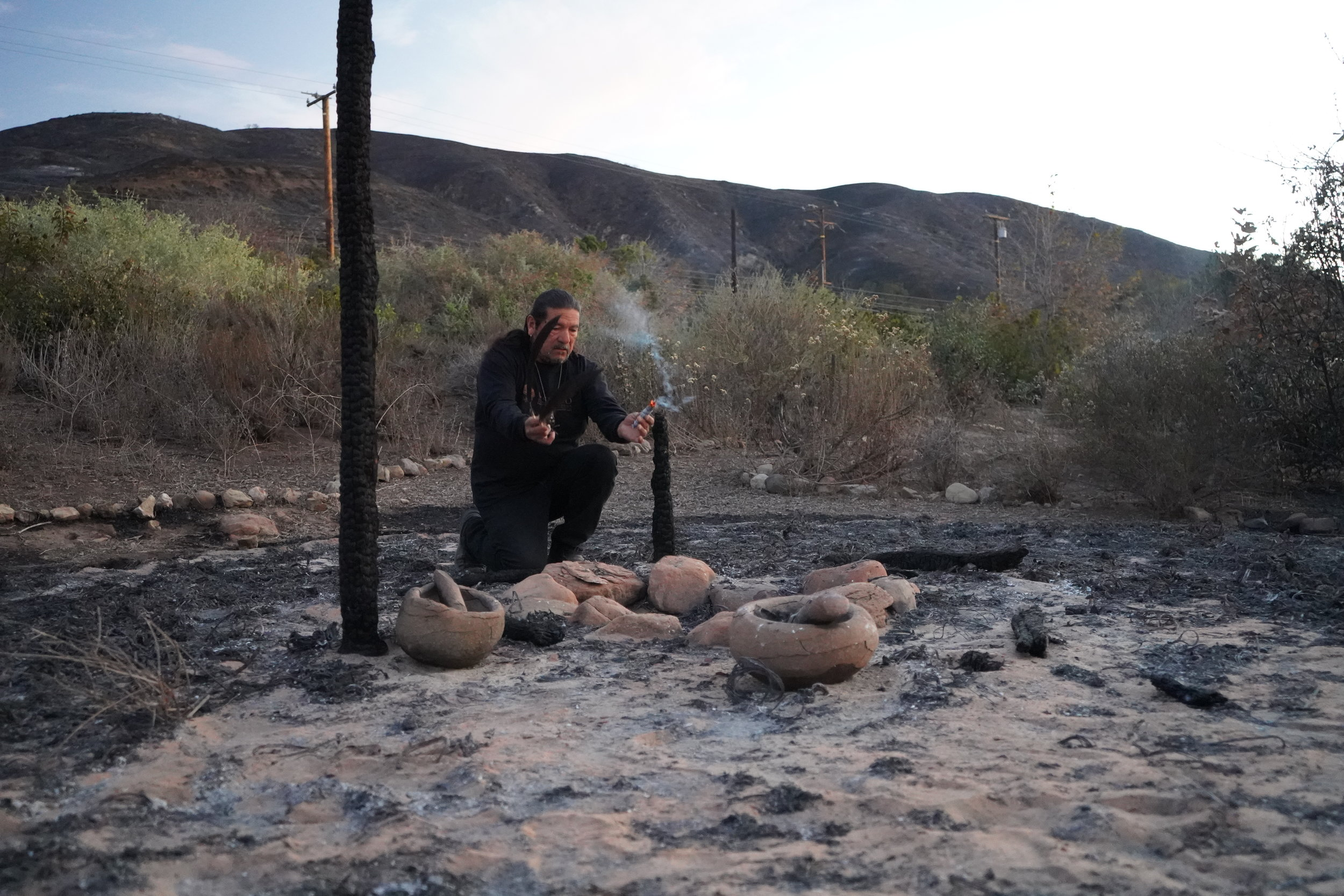 "California wildfires dangerously out of balance    Mati Waiya offers prayers at the site of a burned down 'ap (chumash dwelling) that he built himself and is used as a classroom for 1000s of students each year. It is one of four onsite. ""The stone bowls where just being used to demonstrate oak ecology and uses of acorns for a group of students. We had to evacuate them just the other day. The bowls will crack to the touch and the 'ap is gone,"" he says."