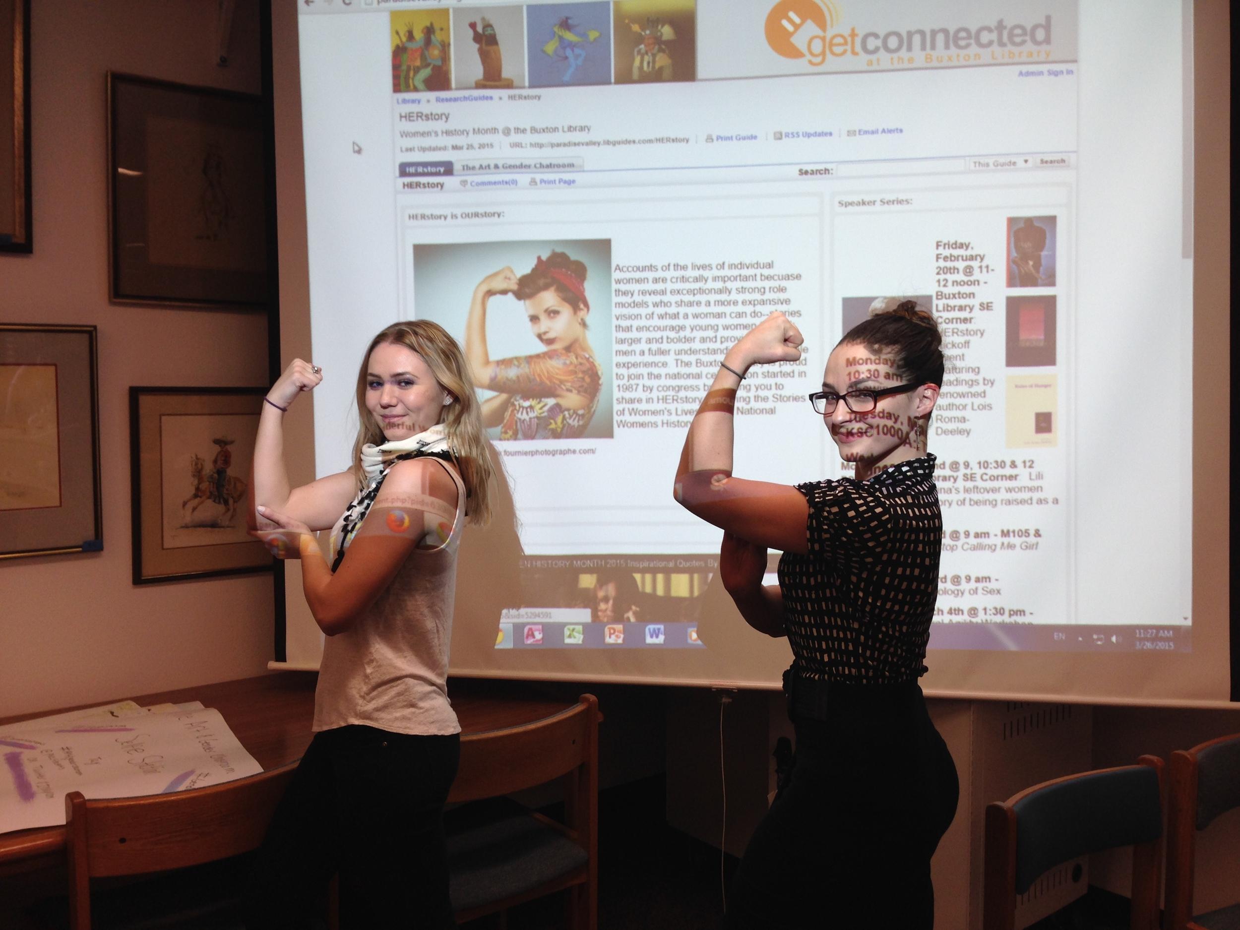 PVCC students Katlynn McNab and Heidi Klotz pose in front of Kande Mickelsen's HERstory blog.