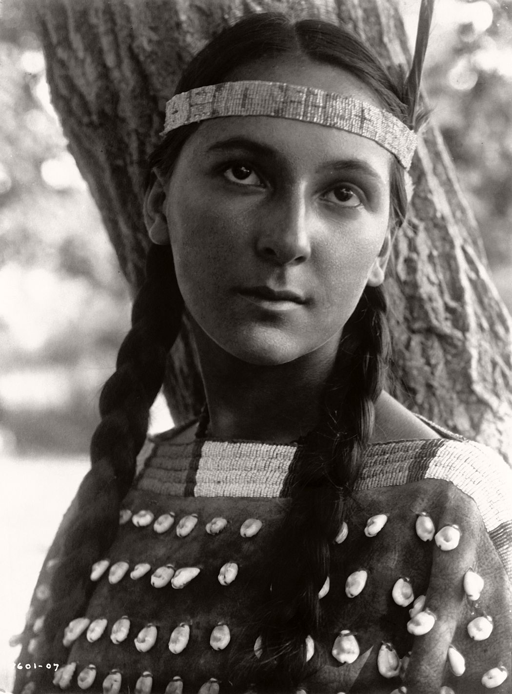 """""""Lucille, portrait of Dakota woman standing in front of tree."""", 1907.  ©EDWARD S. CURTIS/LIBRARY OF CONGRESS"""