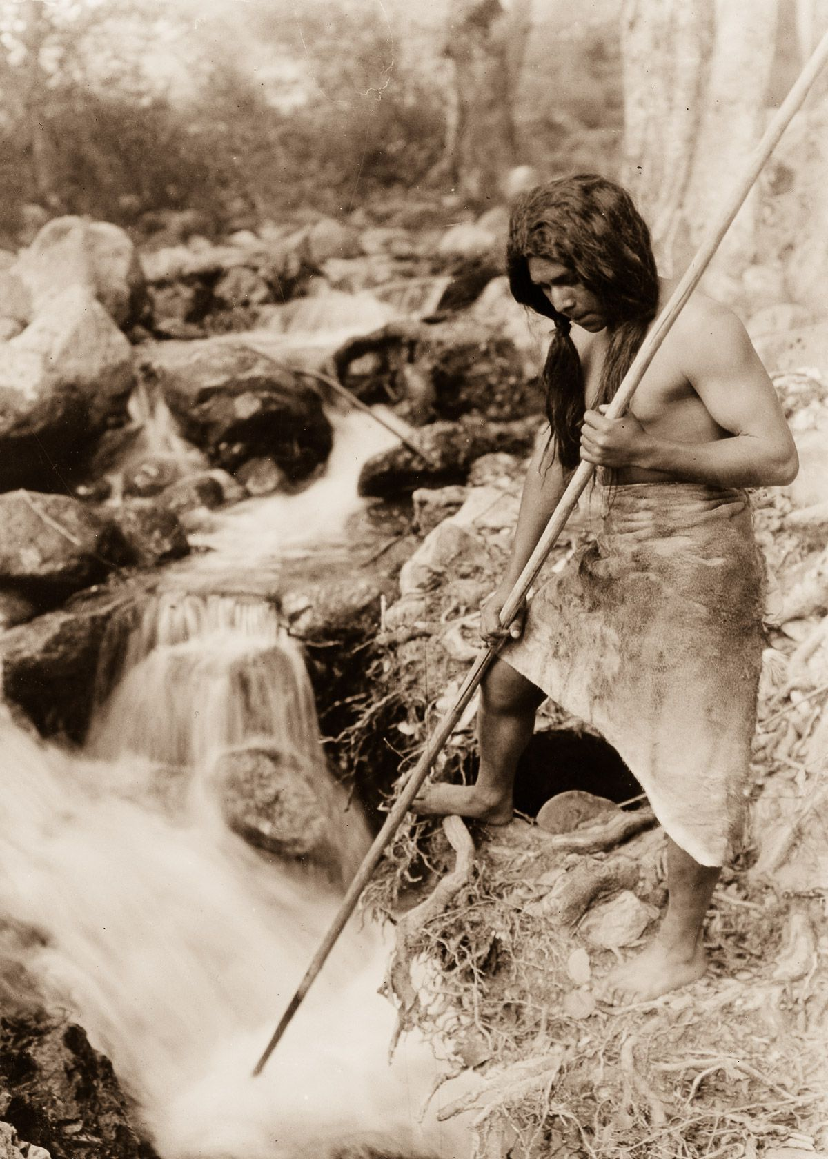 A Hupa spear fisherman watches for salmon,  1923.  ©EDWARD S. CURTIS/LIBRARY OF CONGRESS
