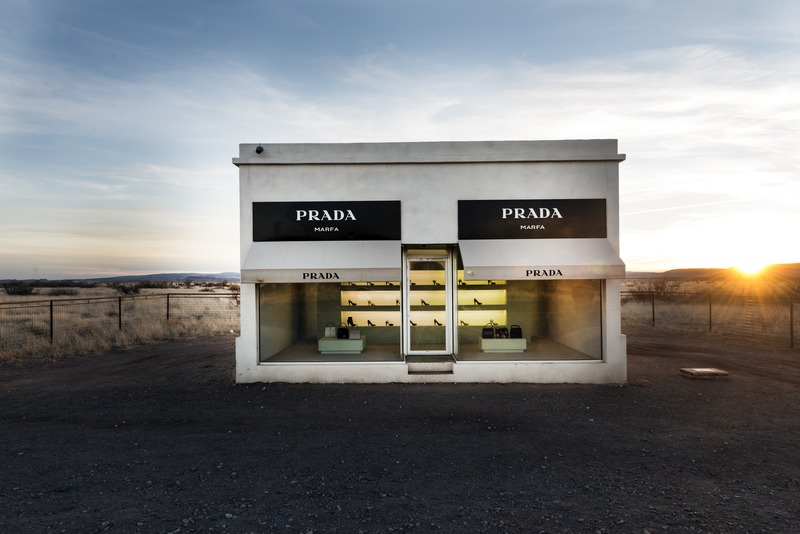 "Prada Marfa is a permanently installed sculpture by artists Elmgreen and Dragset, not in nearby Marfa, Texas, but near the town of Valentine. The installation was inaugurated on October 1, 2005. The artists called the work a ""pop architectural land art project."" The sculpture, completed with the assistance of American architects Ronald Rael and Virginia San Fratello, cost $80,000 and was intended to never be repaired, so that it might slowly degrade back into the natural landscape. This plan was dashed when, three days after the sculpture was completed, vandals graffitied the exterior and broke into the building, stealing handbags and shoes."