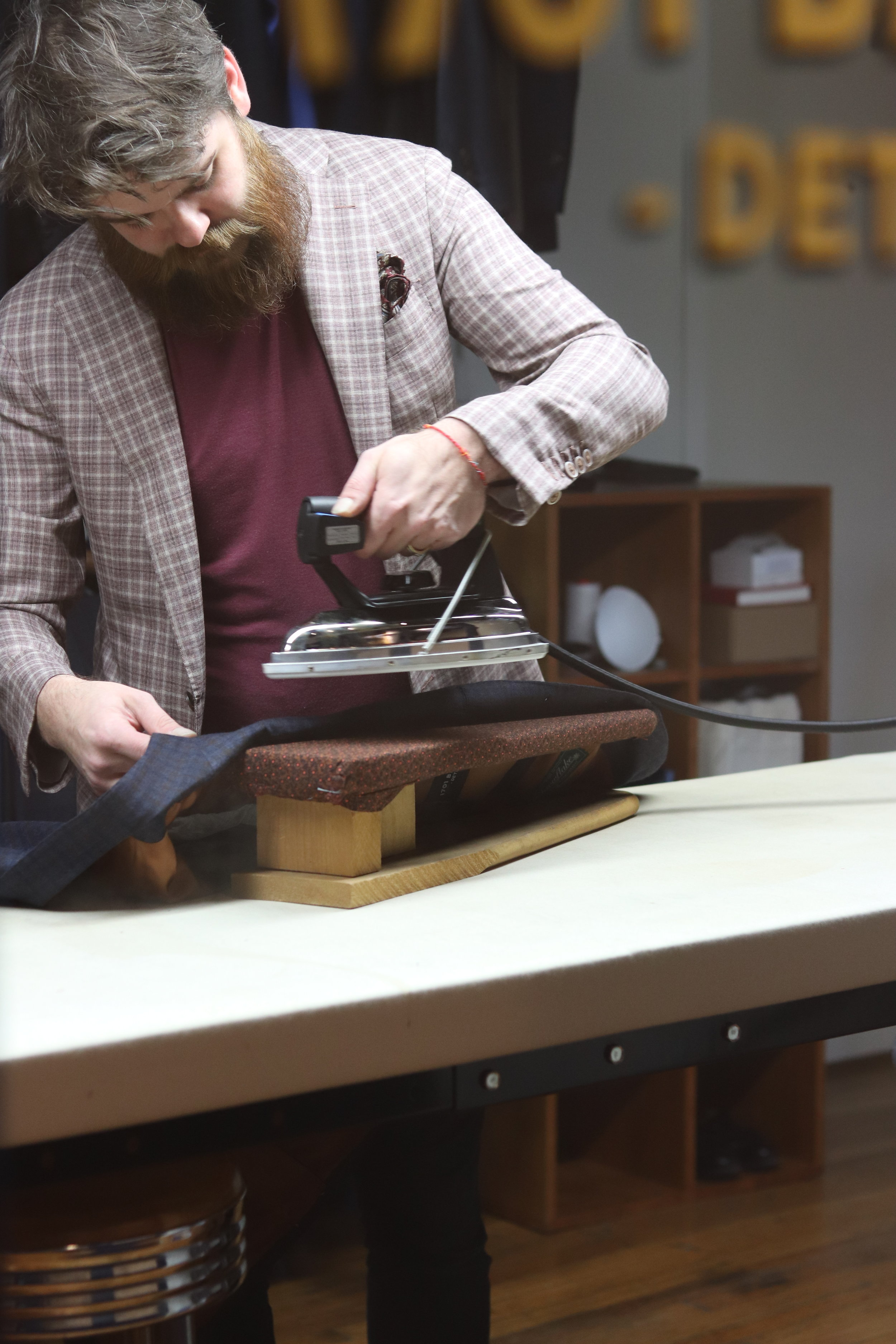 Keith Magna applying a gentle steam to the lapel of a coat.