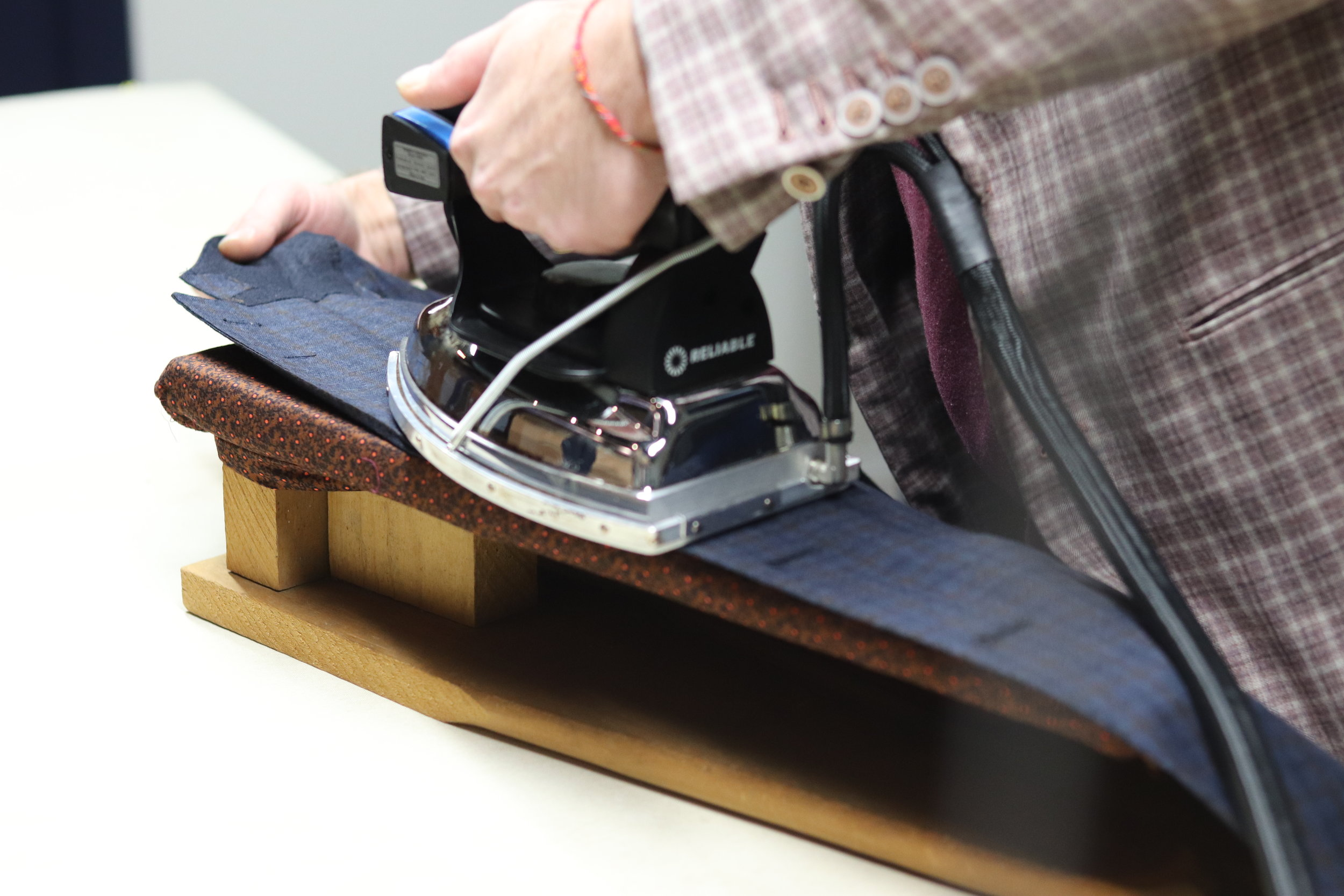 Keith Magna pressing the roll of a lapel.
