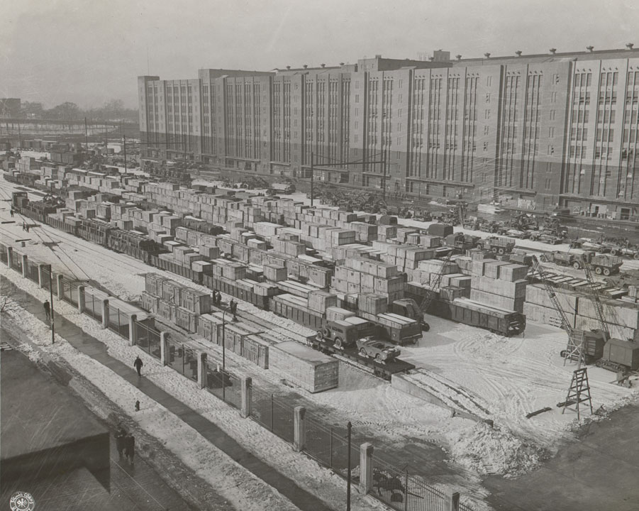 Vehicles and weapons waiting in yards outside Warehouse B, Brooklyn Army Base Terminal, New York Port of Embarkation. US Signal Corp., 1945-1946.  NYC Municipal Archives.
