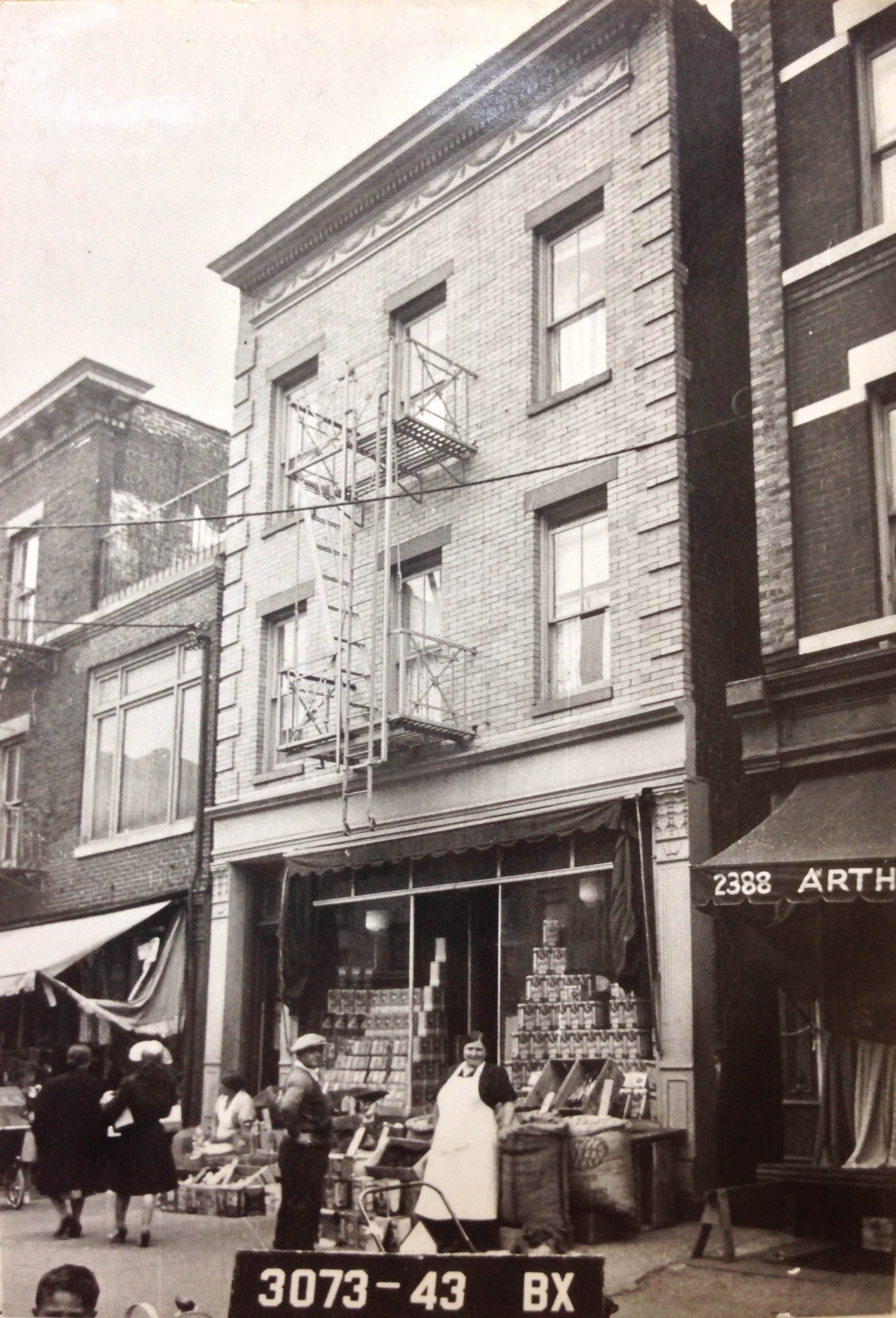 2390 Arthur Avenue, Bronx, circa 1940. In the heart of the Bronx's Little Italy, we see a shop keeper and patron looking directly at the camera as the tax photo is taken.Department of Finance Collection, NYC Municipal Archives.