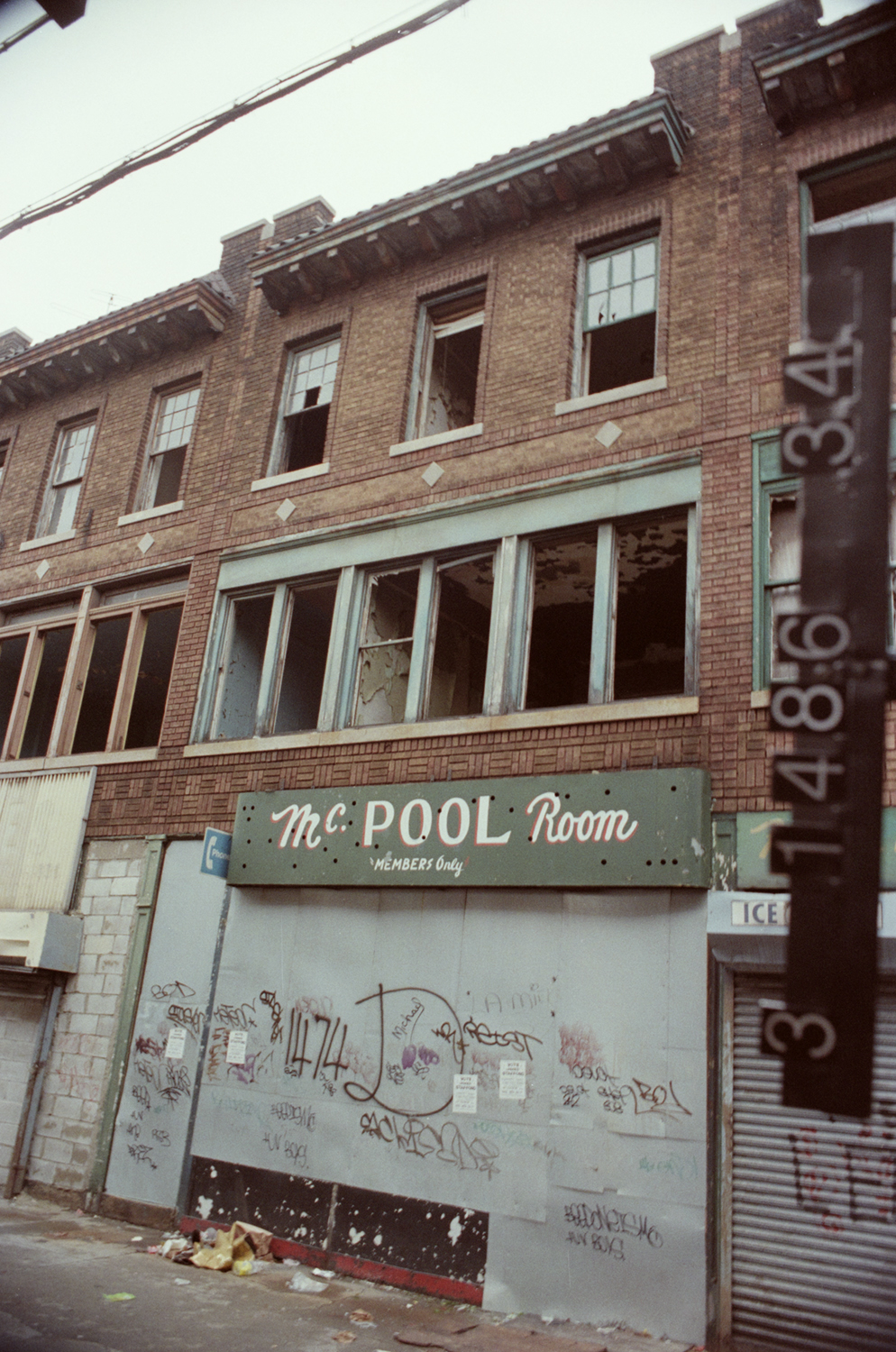 1474 Broadway in the 1980s seen here as a vacant pool hall, the window exteriors are the same as the 1940s building, but the main difference being they're shattered . Department of Finance Collection, NYC Municipal Archives.
