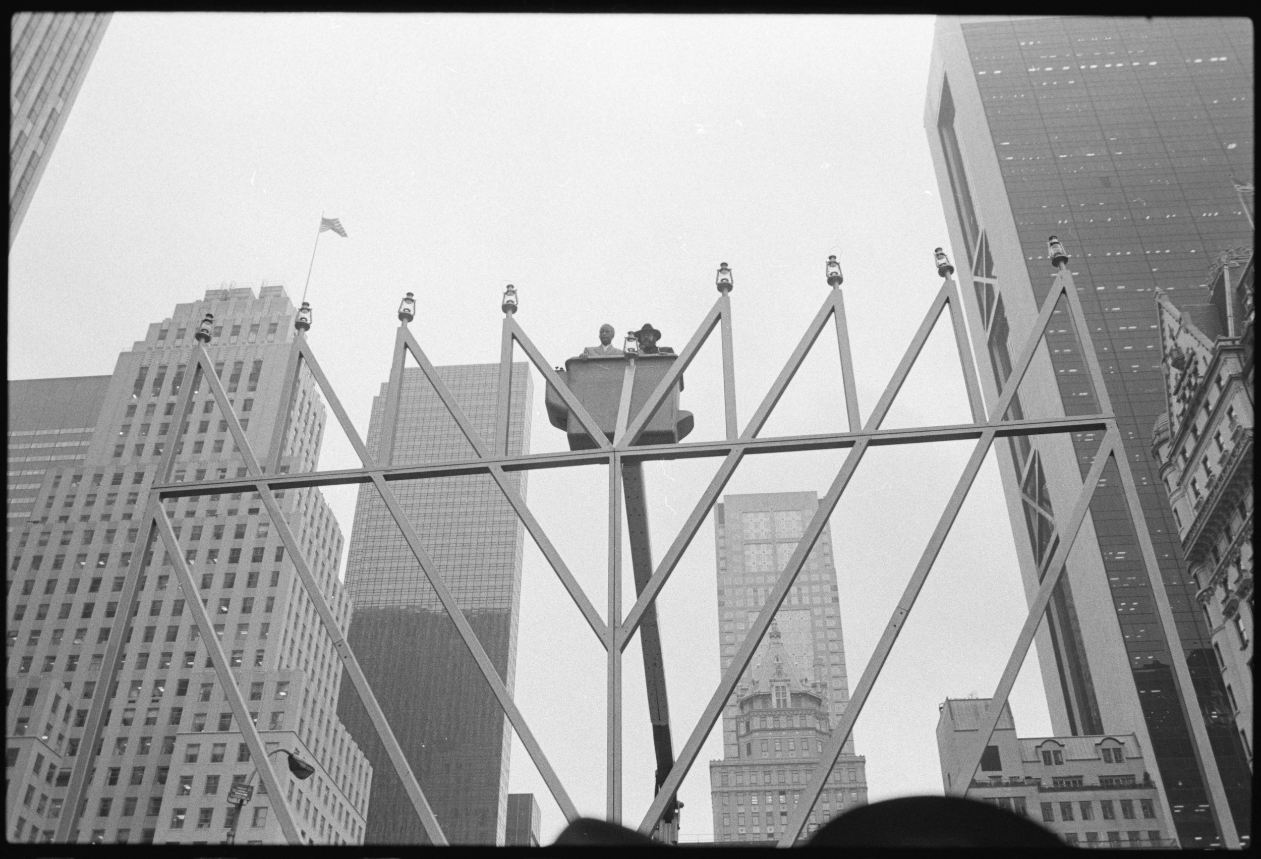 Mayor David Dinkins and Rabbi Shmewl Butman are lifted in a Con Edison cherry-picker to light the world's largest Menorah in Grand Army Plaza at 59th Street Manhattan. Mayor Dinkins Collection, NYC Municipal Archives.