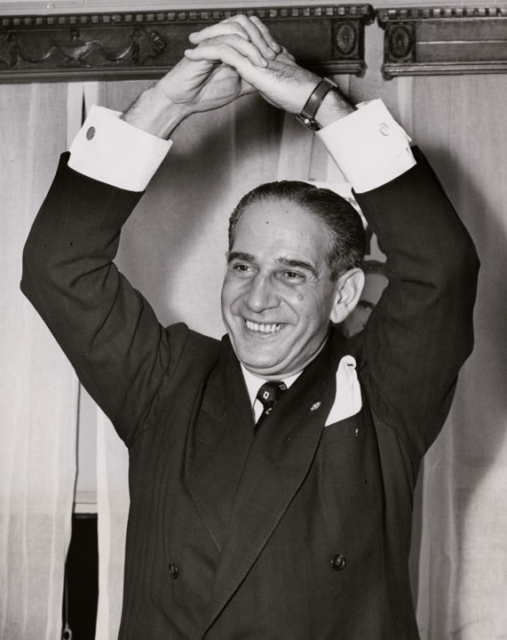 Newly elected Mayor Vincent R. Impellitteri gives a Victory Handshake at his headquarters in the Hotel Abbey on November 7, 1950.  Impellitteri became Acting Mayor on September 2, 1950, upon the resignation of Mayor William O'Dwyer and won a full four-year term in a special election on November 7, 1950.  ACME News Photos, Mayor Wagner Papers, NYC Municipal Archives.