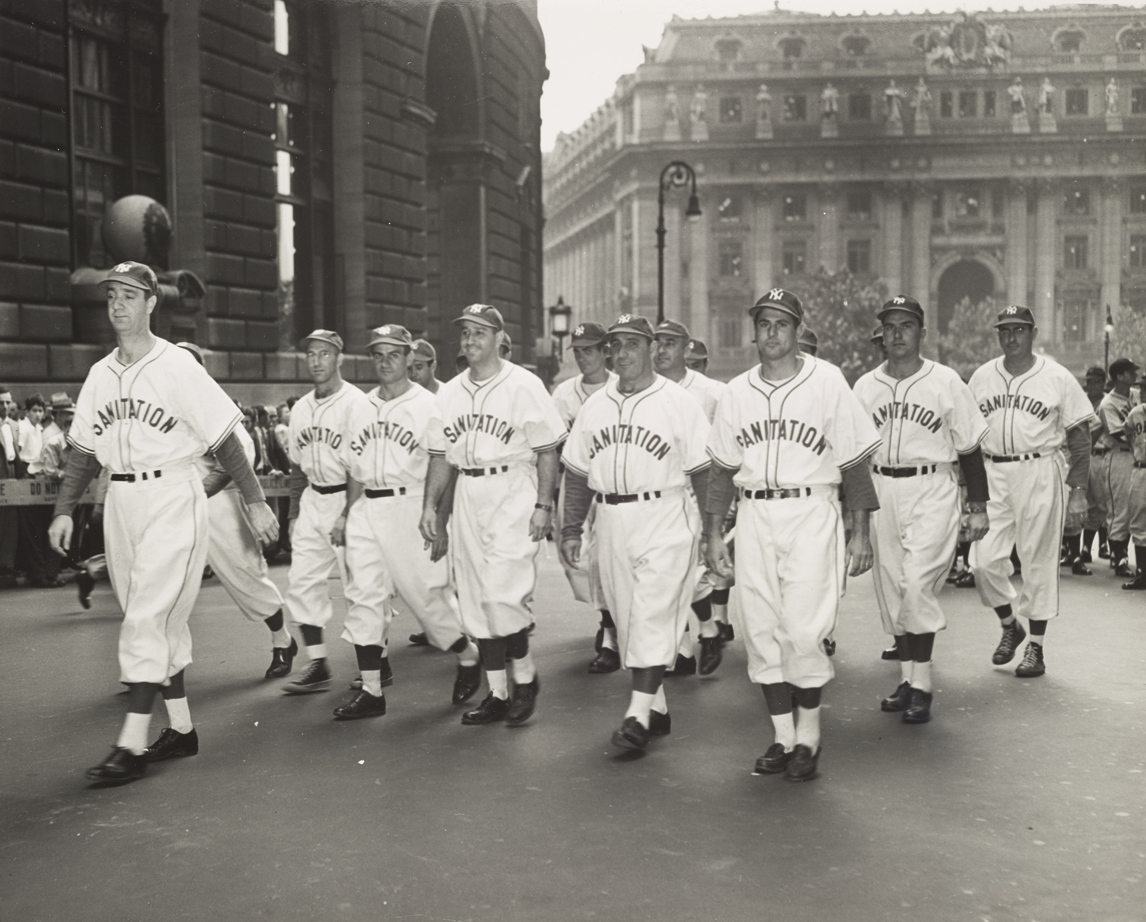 Sanitation Department Baseball Team marches on Lower Broadway on Connie Mack Day, August 19, 1949. NYC Municipal Archives Collections.