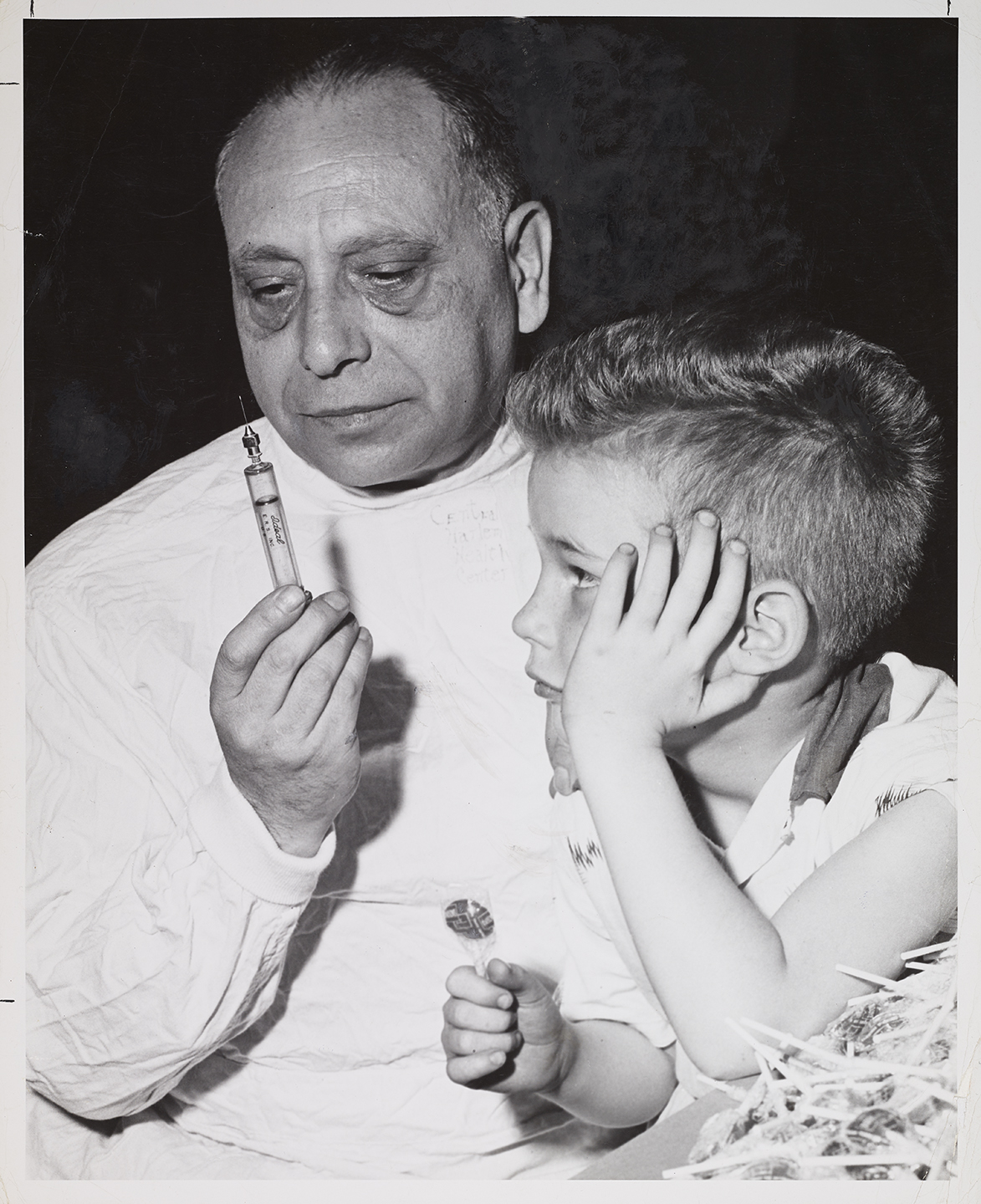 Boy with post-vaccine lollipop reward poses with doctor, 1955. Department of Health Collection, NYC Municipal Archives.