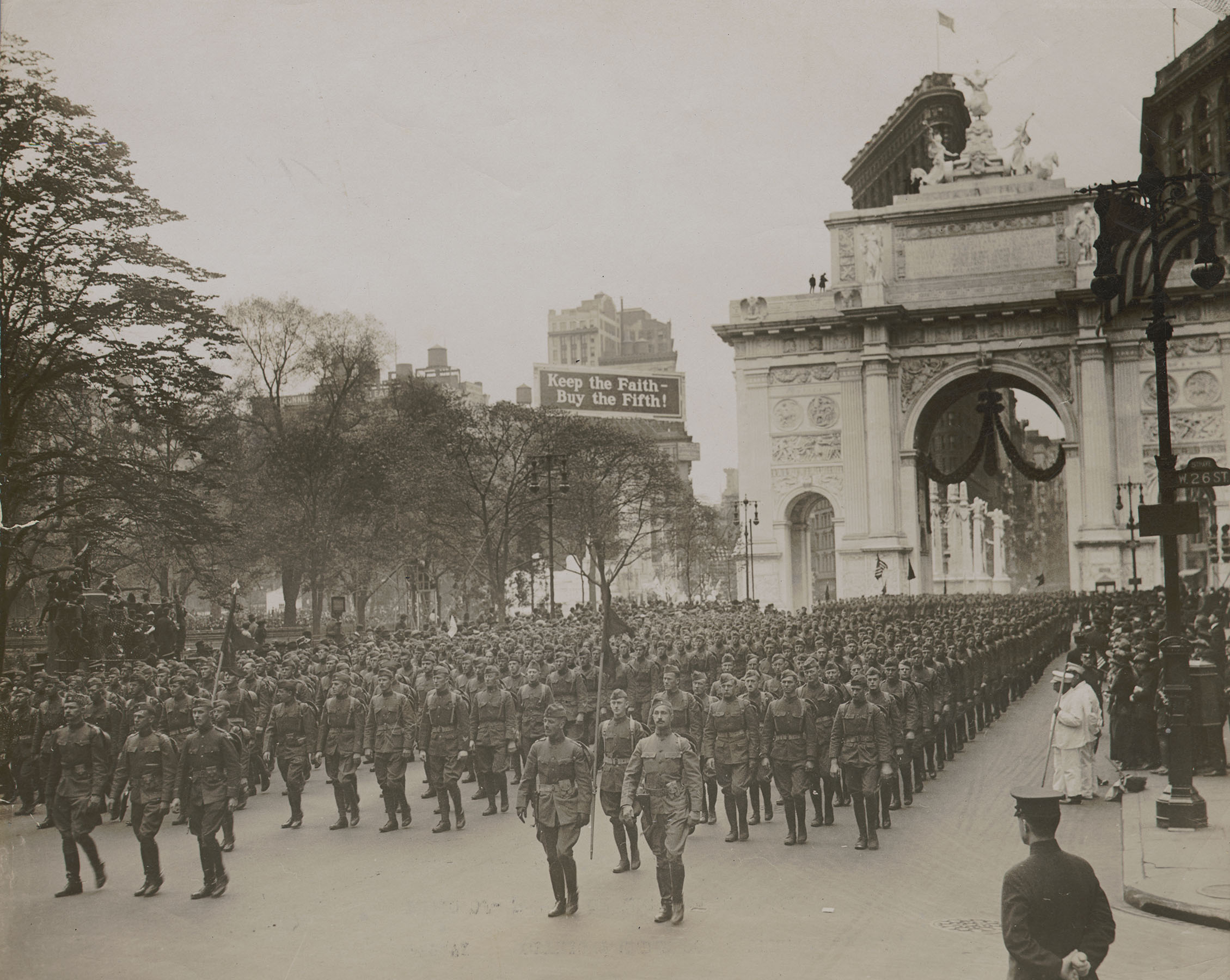 Parade of the 77th Division, 1919. General view of the parade showing a company passing through the Victory Arch at Madison Square in mass formation, the same formation used by the Division in their review before General Pershing. Underwood & Underwood. Mayor's Reception Committee, NYC Municipal Archives.