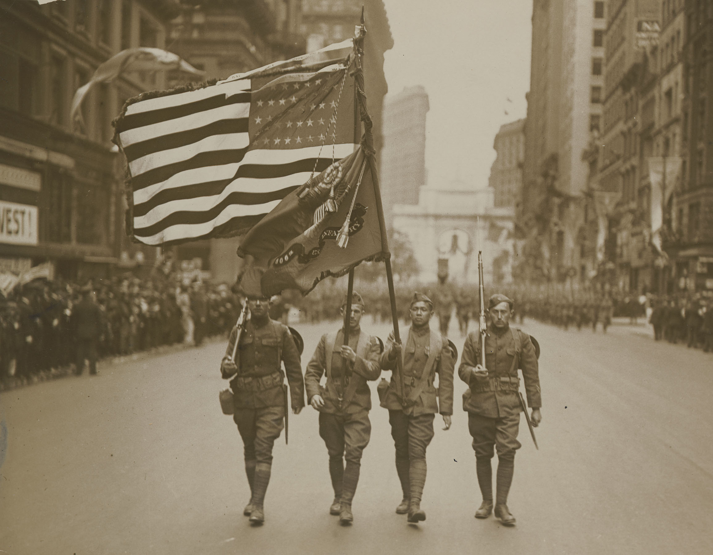 Parade of the 77th Division, May 6, 1919. Color sergeant Sing Kee (2nd from right), was awarded the Distinguished Service Cross and the French Croix de Guerre. He was the first Chinese American to be decorated for bravery. Underwood & Underwood. Mayor's Reception Committee, NYC Municipal Archives.