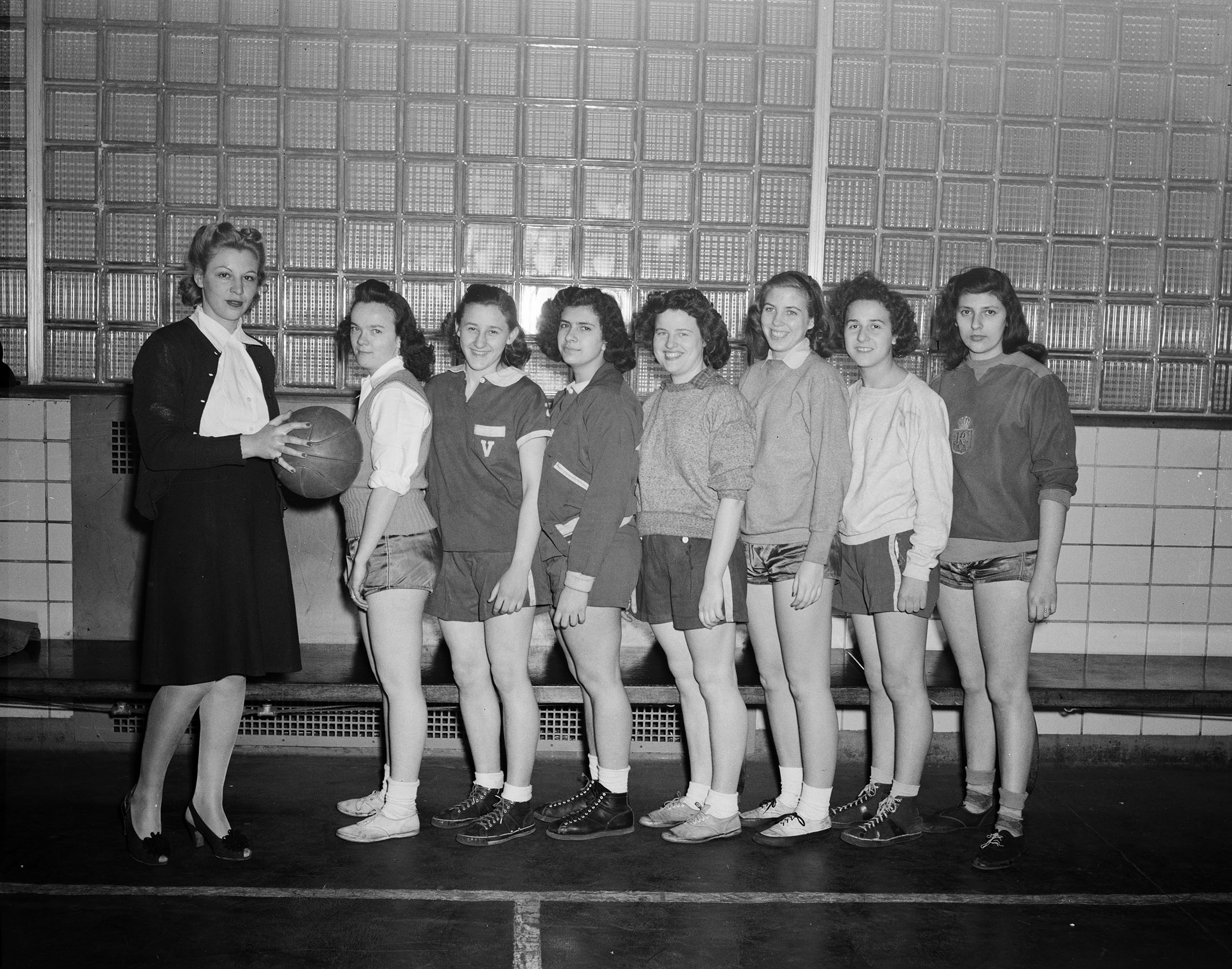 DPR_24008: Basketball tournament Betsy Head at McCarren Park Playground. Coach Caral Deimling, Margaret Hylend, Roseanna Brica, Jean Percella, Theresa McGuire, Ann Bousson, Theresalinn Vaccaro, Estell Kestenbaum, March 9, 1945. Department of Parks and Recreation Collection, NYC Municipal Archives.