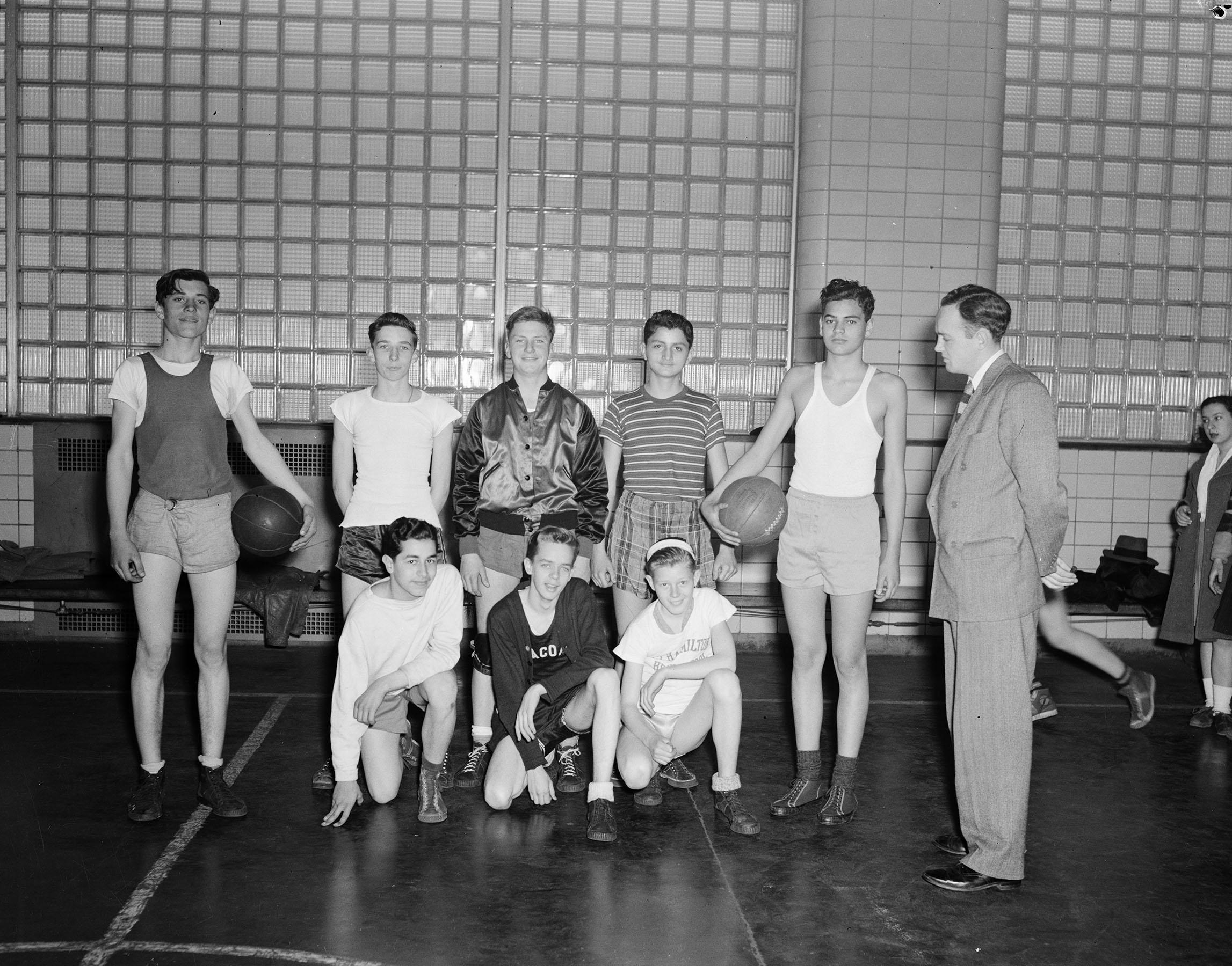 DPR_24011: Basketball Betsy Head Boys Team: (Fort Hamilton High School Playground) 1st row L-R Eugene Howie, Roy DeVines, Robert Petter, 2nd Row Jimmy Sotis- Lon MacDonald-Edward Murphy- Howard Weiss- Adam Kalfaian. Coach Tom Burns, March 9, 1945