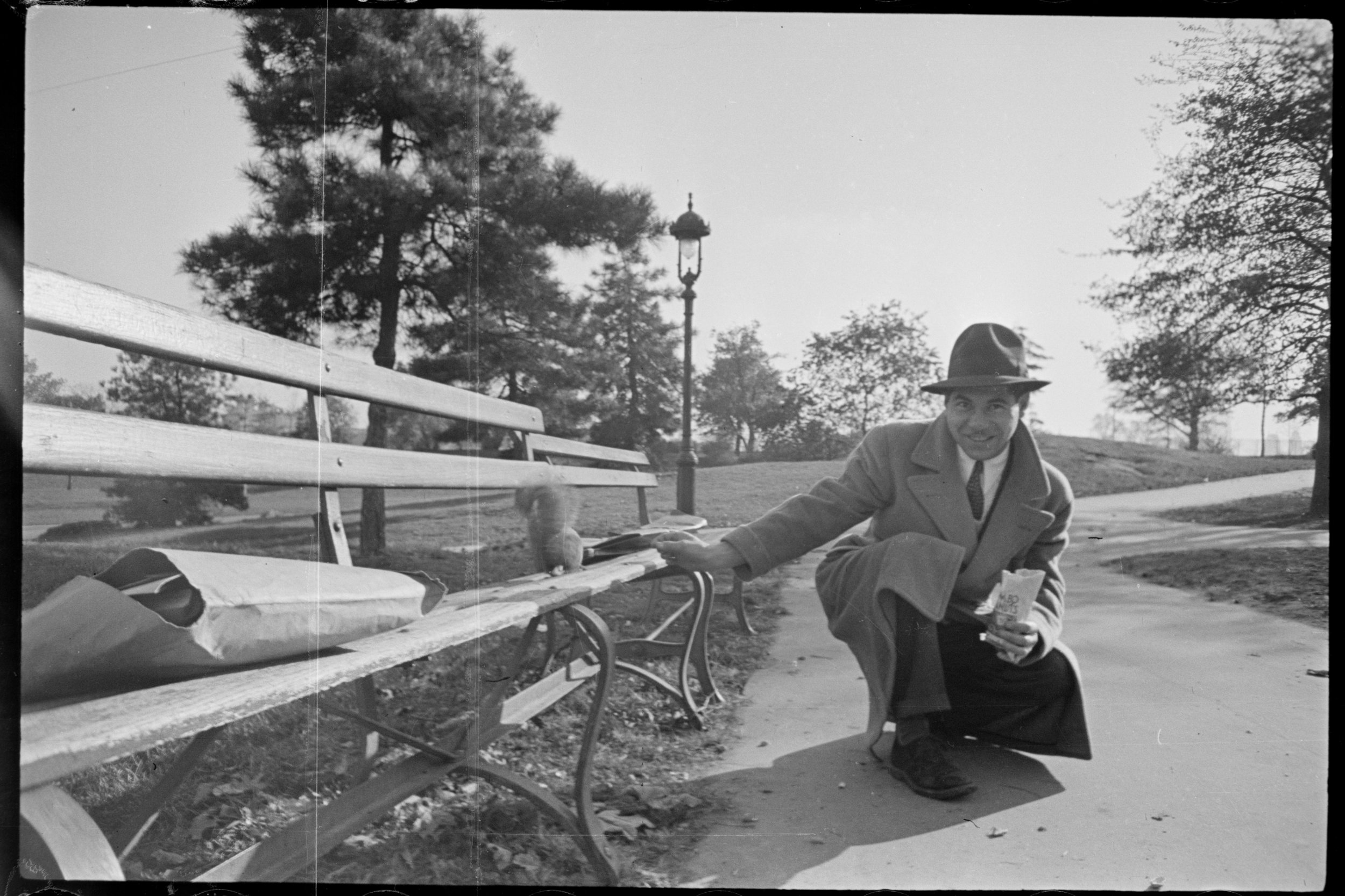 A Tax Department clerk feeding a squirrel in Central Park, ca. 1940.