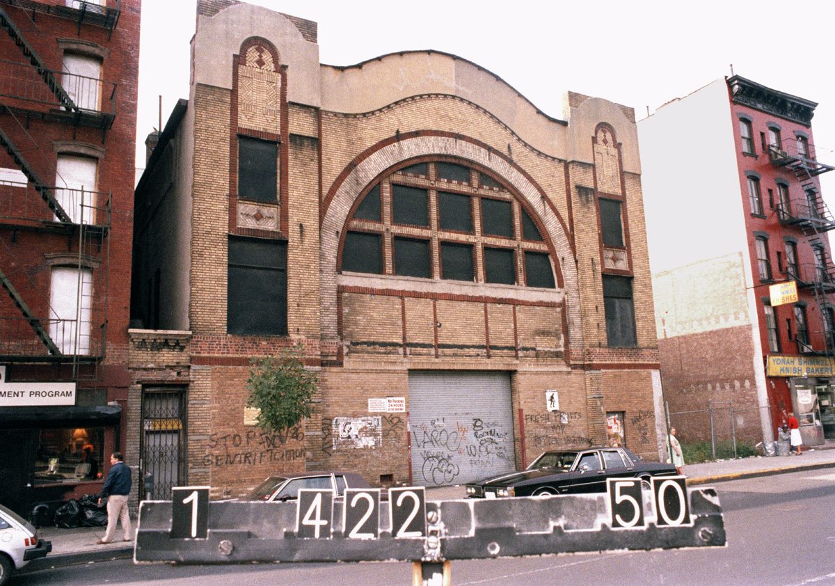 "The Sunshine Movie Theater on Houston Street, which was being used as a warehouse in the mid-1980s. Note the graffiti: ""Stop Gentrification."" If they only knew. DOF Tax Photograph Collection, NYC Municipal Archives."