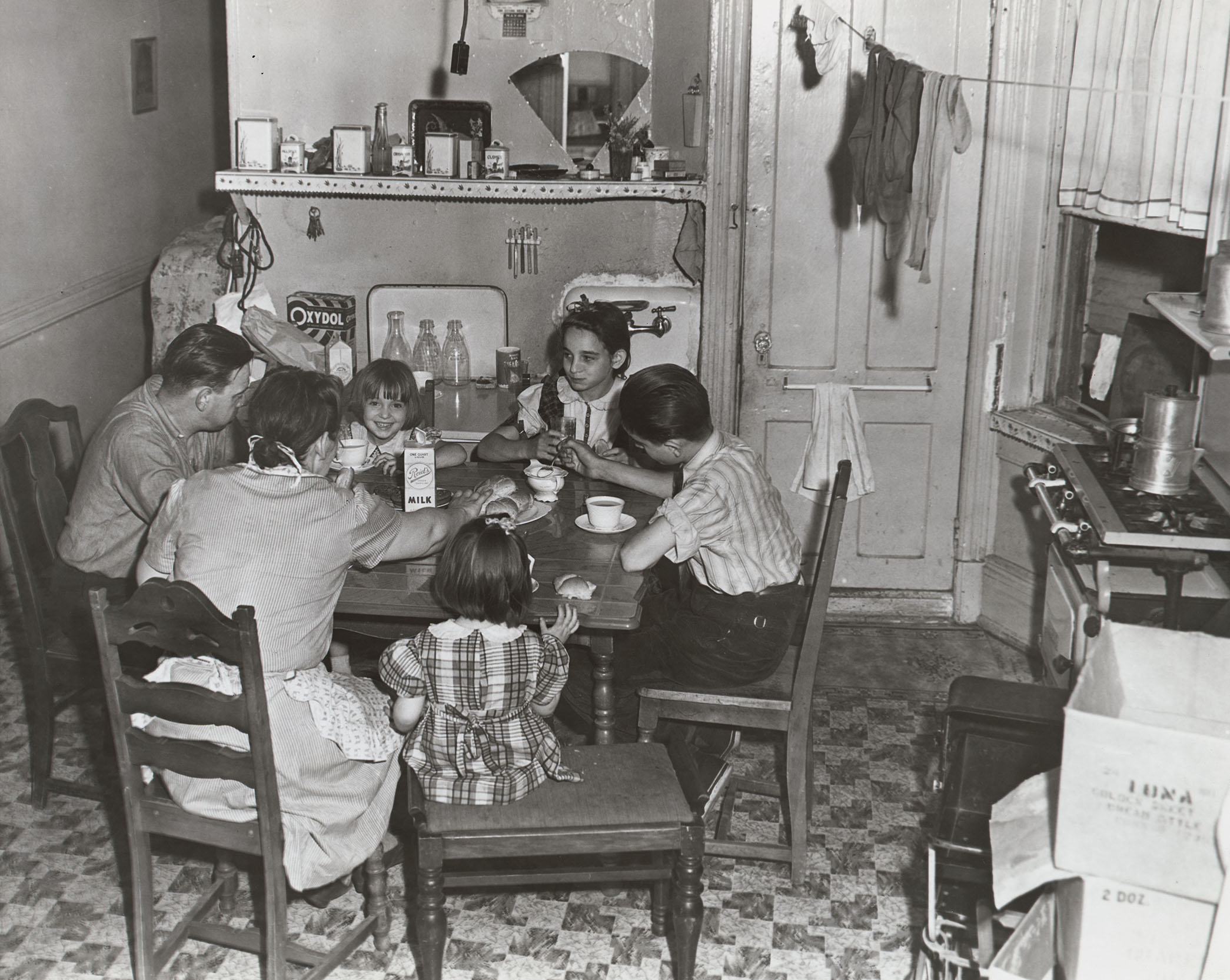 "Family at kitchen table in a dumb-bell ""New Law"" tenement, ca. 1935. Note the angled kitchen window onto an air shaft. NYC Municipal Archives Collection."