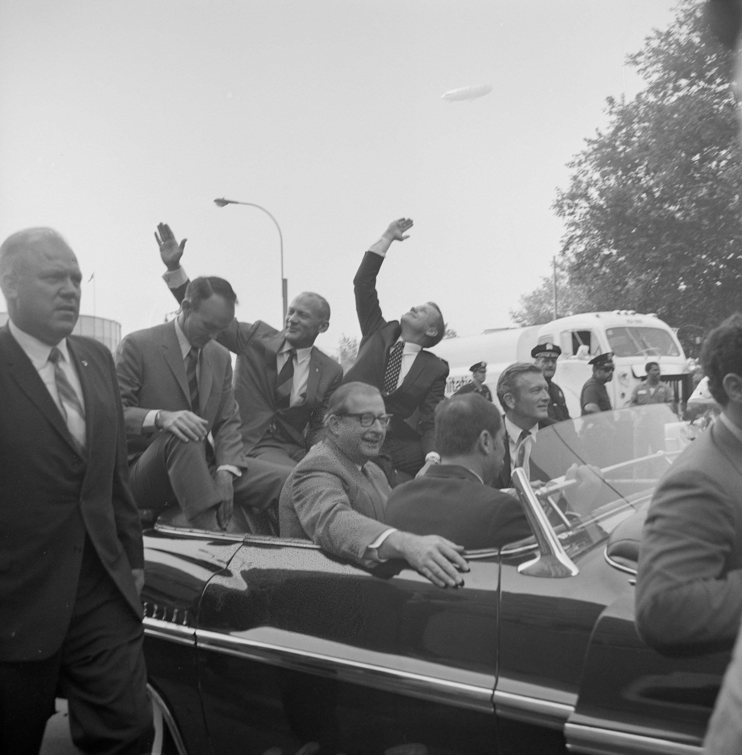 Seated on the custom-built Chrysler Imperial parade limousine, L-R: Apollo 11 astronauts Neil A. Armstrong, Col. Buzz Aldrin, Lt. Col. Michael Collins, wave to onlookers. Mayor Lindsay is seated at right, August 13, 1969. Department of Sanitation Collection, NYC Municipal Archives.