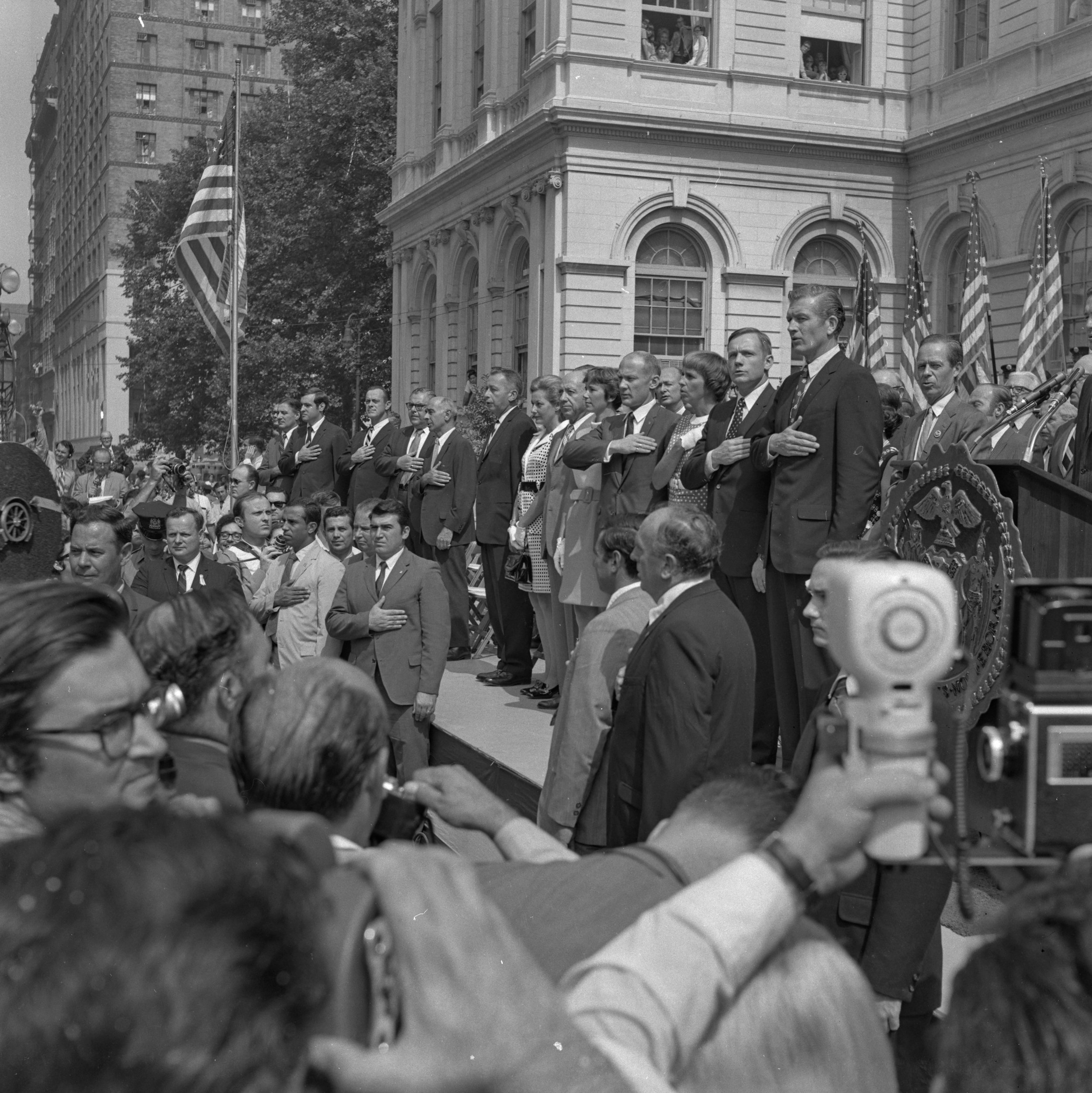 City officials, Apollo 11 Astronauts, and their families recite the pledge of allegiance on the steps of City Hall, August 13, 1969. NYPD Collection, NYC Municipal Archives.
