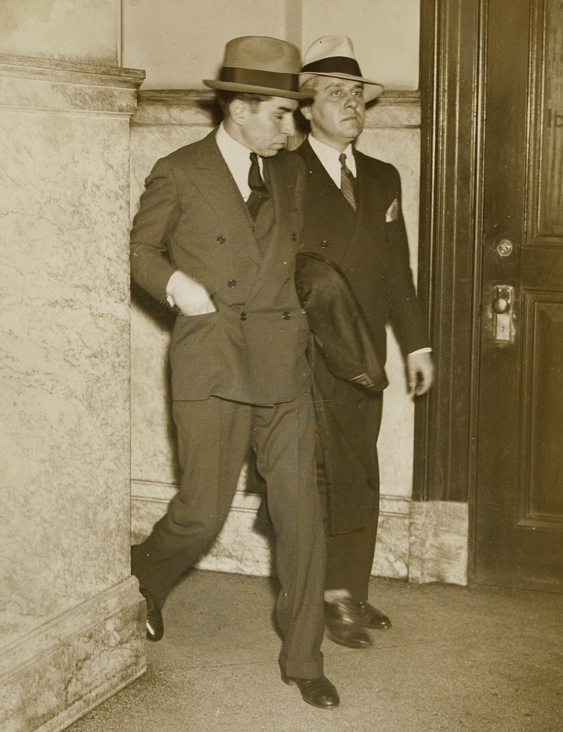Lucky Luciano (left) enters police headquarters with detective on arrival from Little Rock, April 18, 1936. NYC Municipal Archives Collection.