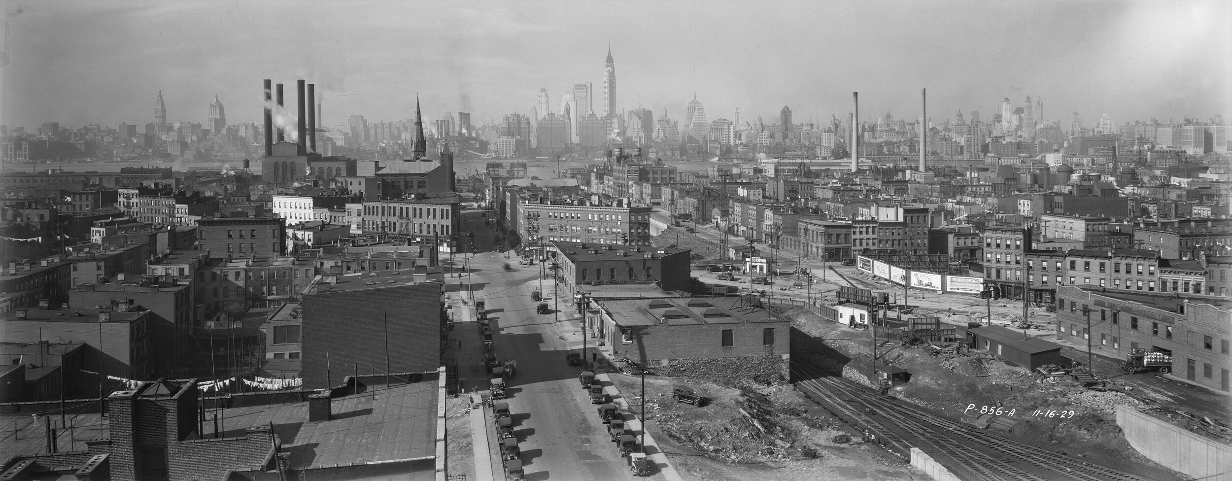 P-856-a:  Elevated view of Long Island City, November 16, 1929. The Chrysler Building is at the center of the Manhattan skyline. Borough President Queens Collection, NYC Municipal Archives.
