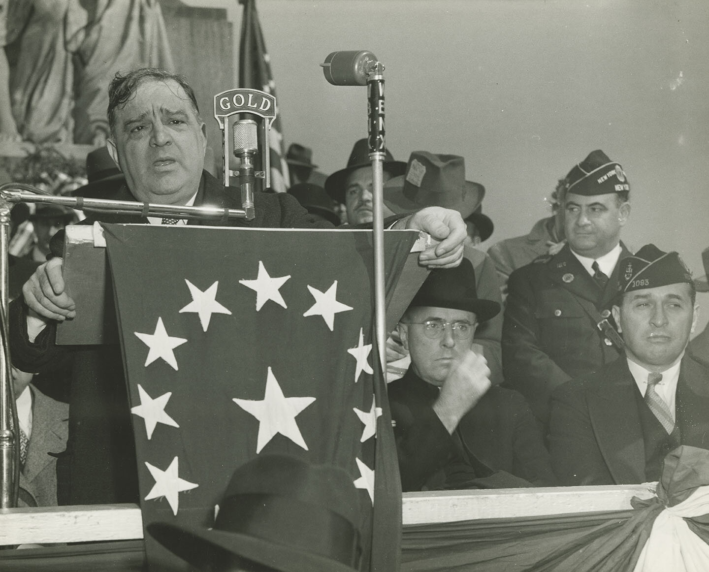 Mayor LaGuardia speaking at reviewing stand, at the Columbus Day Parade, October 12, 1943. Mayor LaGuardia Collection, NYC Municipal Archives.