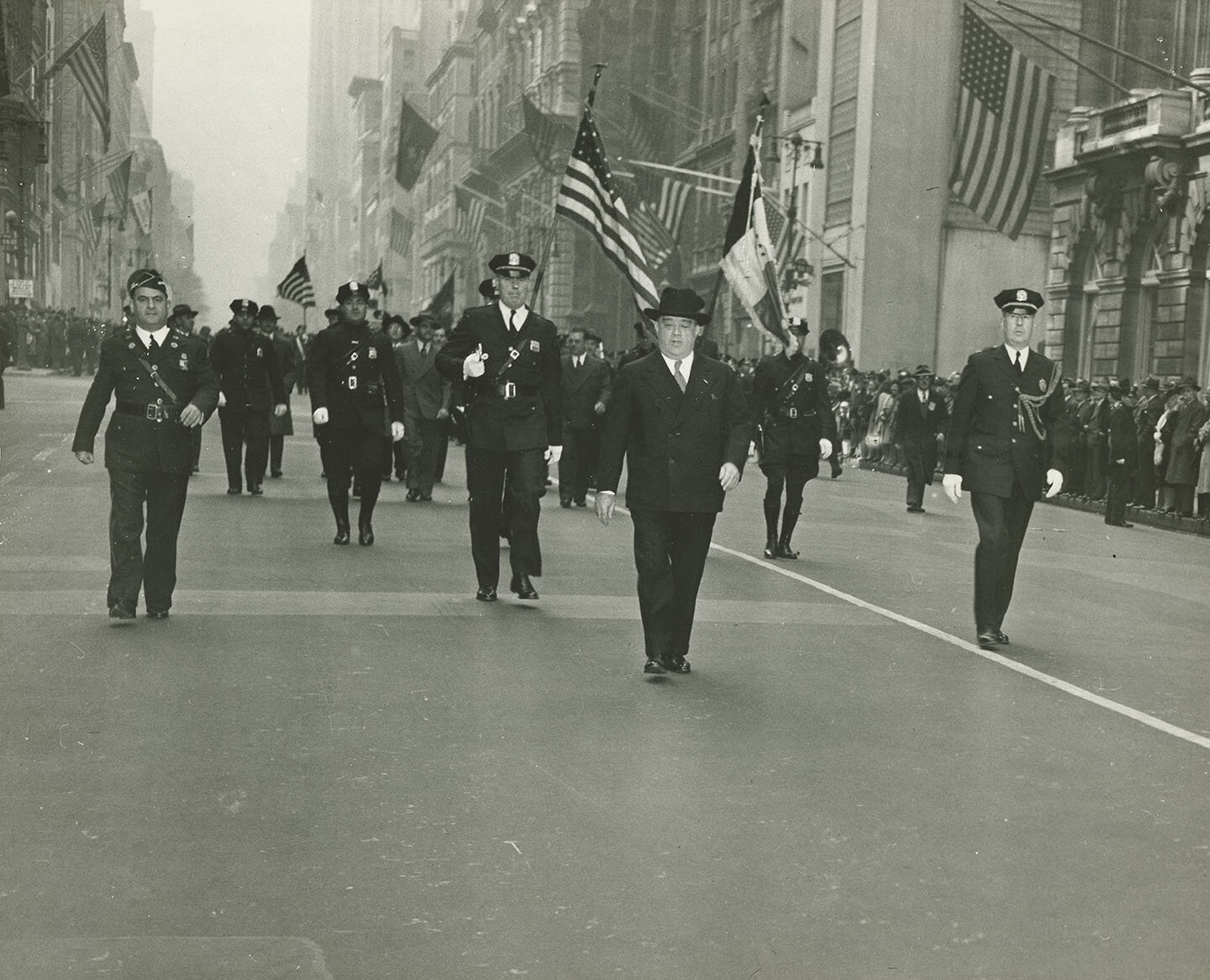 Mayor LaGuardia marching at head of Columbus Day Parade, flanked and followed by policemen, October 12, 1943. Mayor LaGuardia Collection, NYC Municipal Archives.
