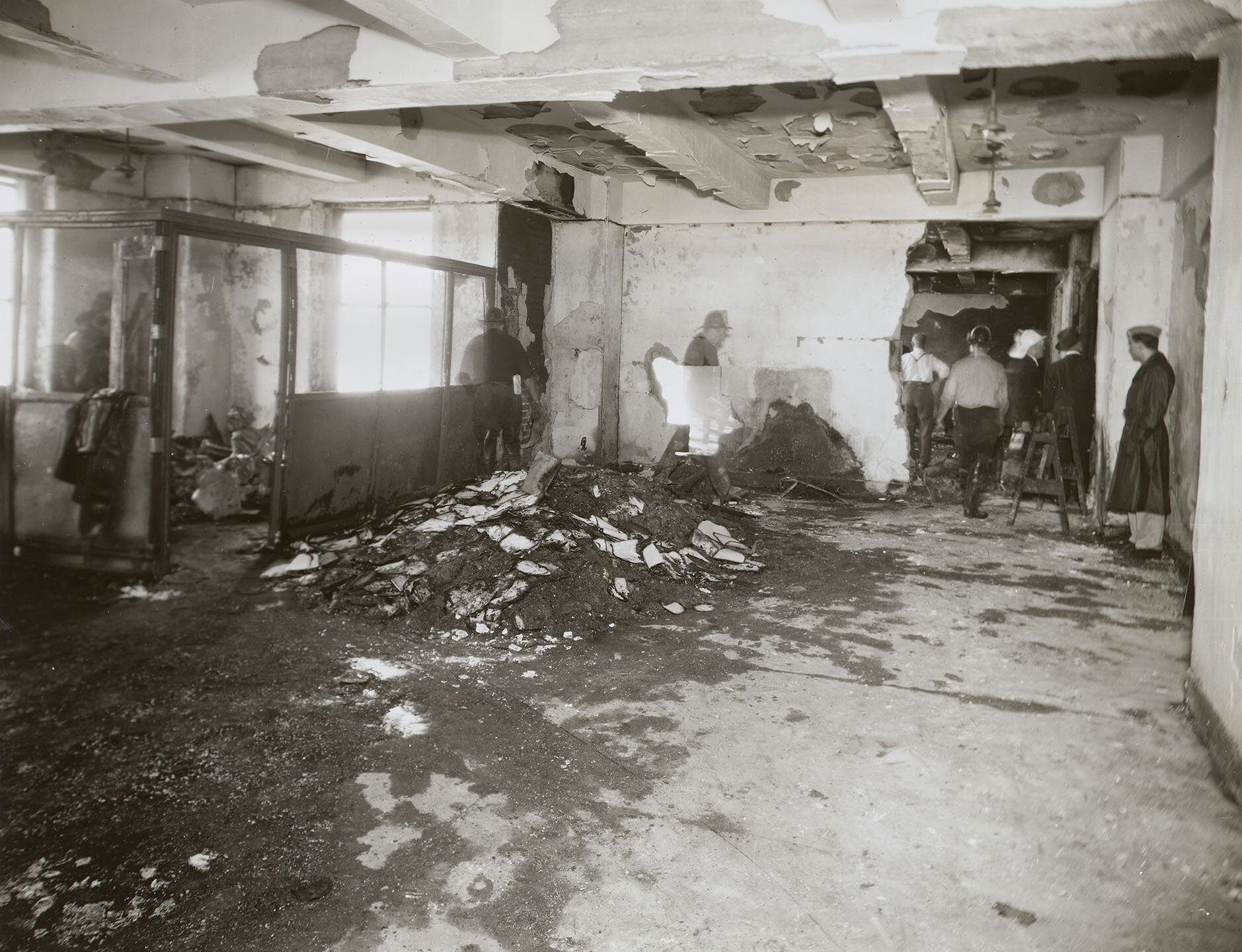 Empire State Building Disaster: Interior, W side of 79th Fl, facing E; 12:30 pm, July 28, 1945. Firemen walking through rubble in rear. Mayor LaGuardia Collection, NYC Municipal Archives.