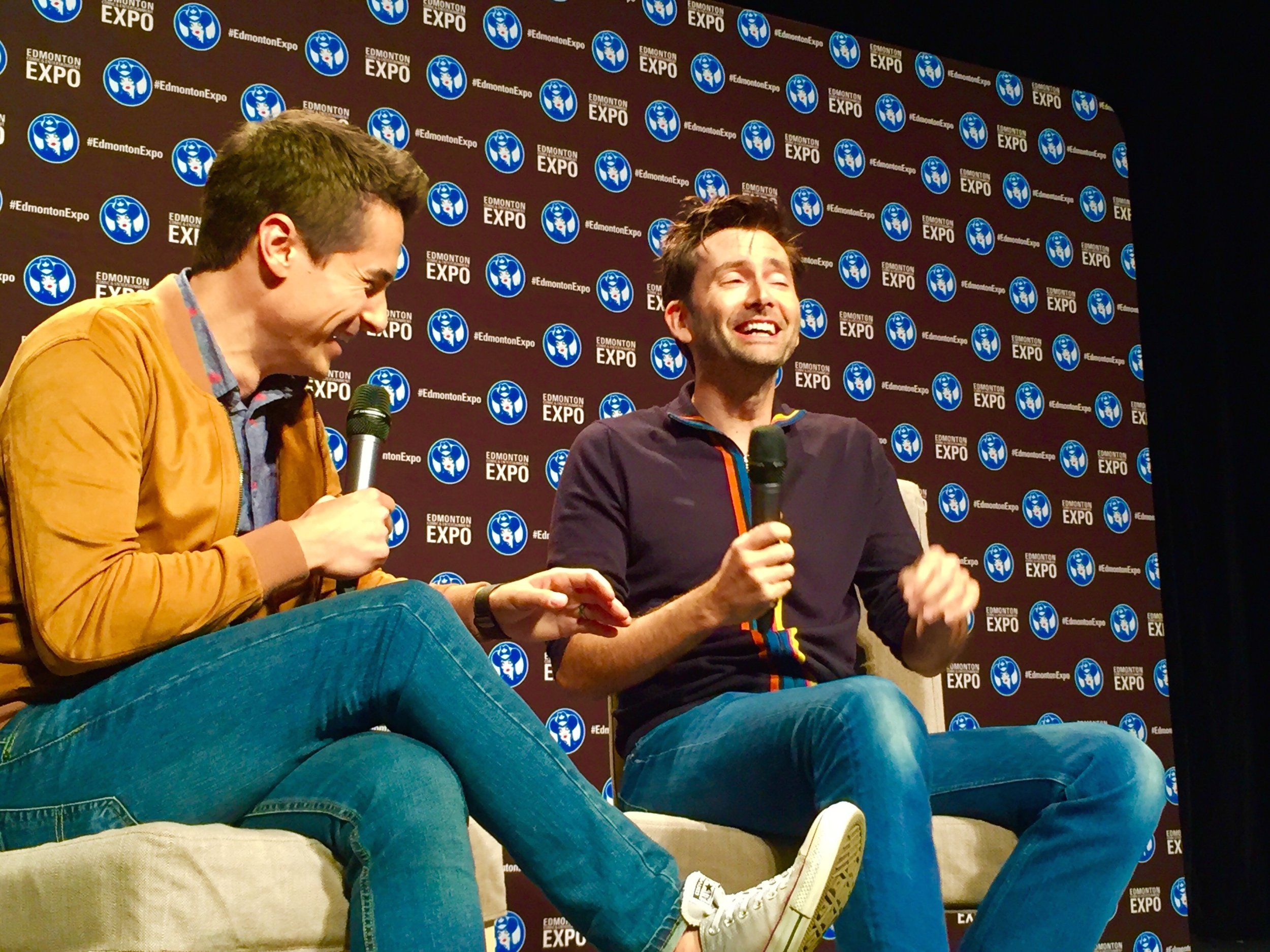 Tanner Zipchen moderating a panel with David Tennant at the 2018 Edmonton Expo.   (Photo credit: Charles Cousins for GeekNerdNet.com)