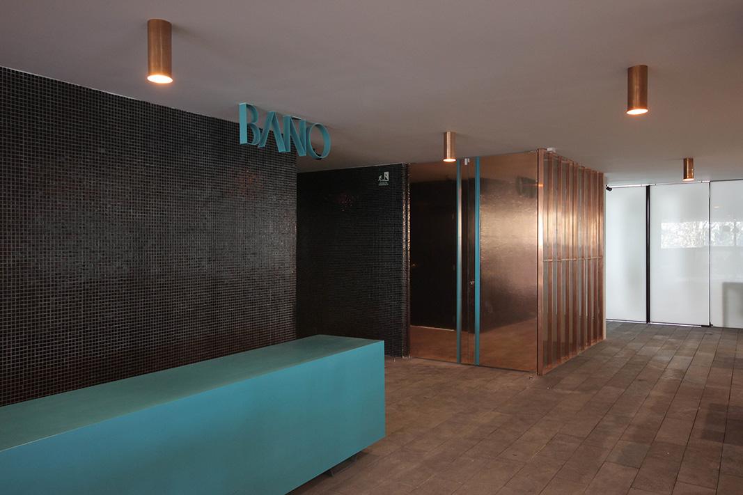 una puerta de cobre va registrando –absorbiendo huellas digitales en su superficie - la presencia de cada usuario que va compartiendo el espacio