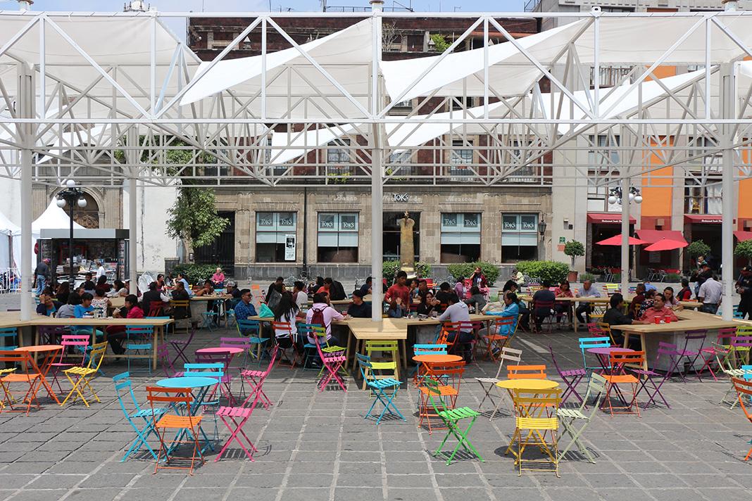 De cada columna de soporte se extienden mesas de madera a 120 grados y se ofrecen múltiples sillas de color para que la gente pueda ir escogiendo donde sentarse.