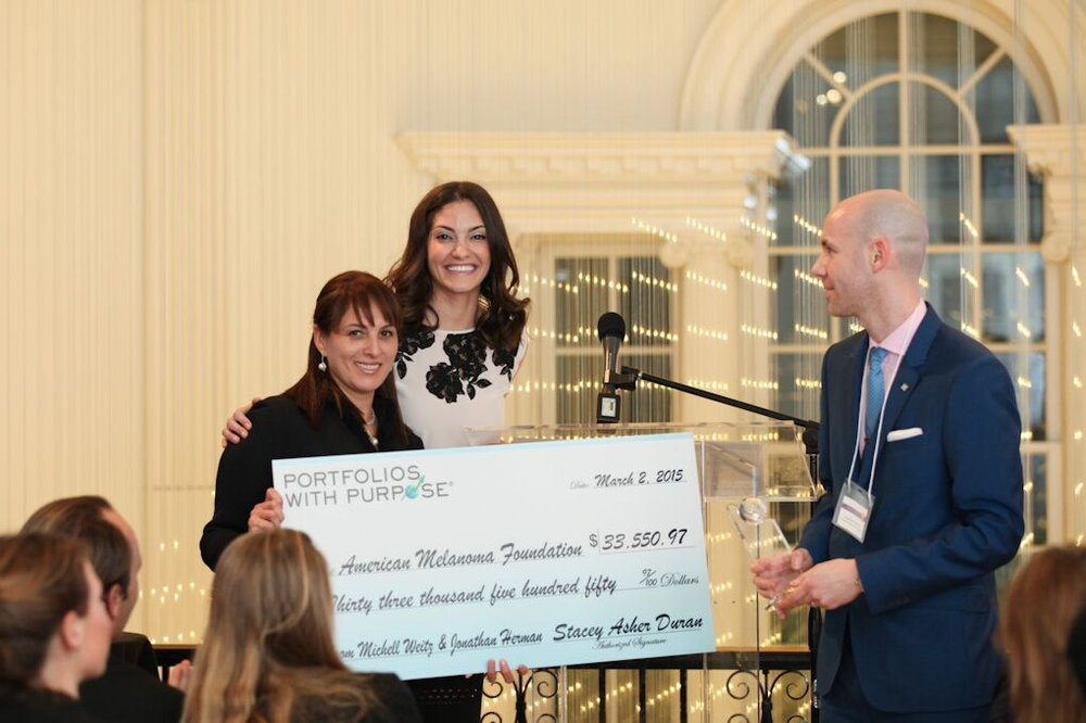 Dr. Mona Mofid receiving a donation on behalf of the American Melanoma foundation at the 2015 Portfolios with Purpose award ceremony with Stacey Asher and Jonathan Herman