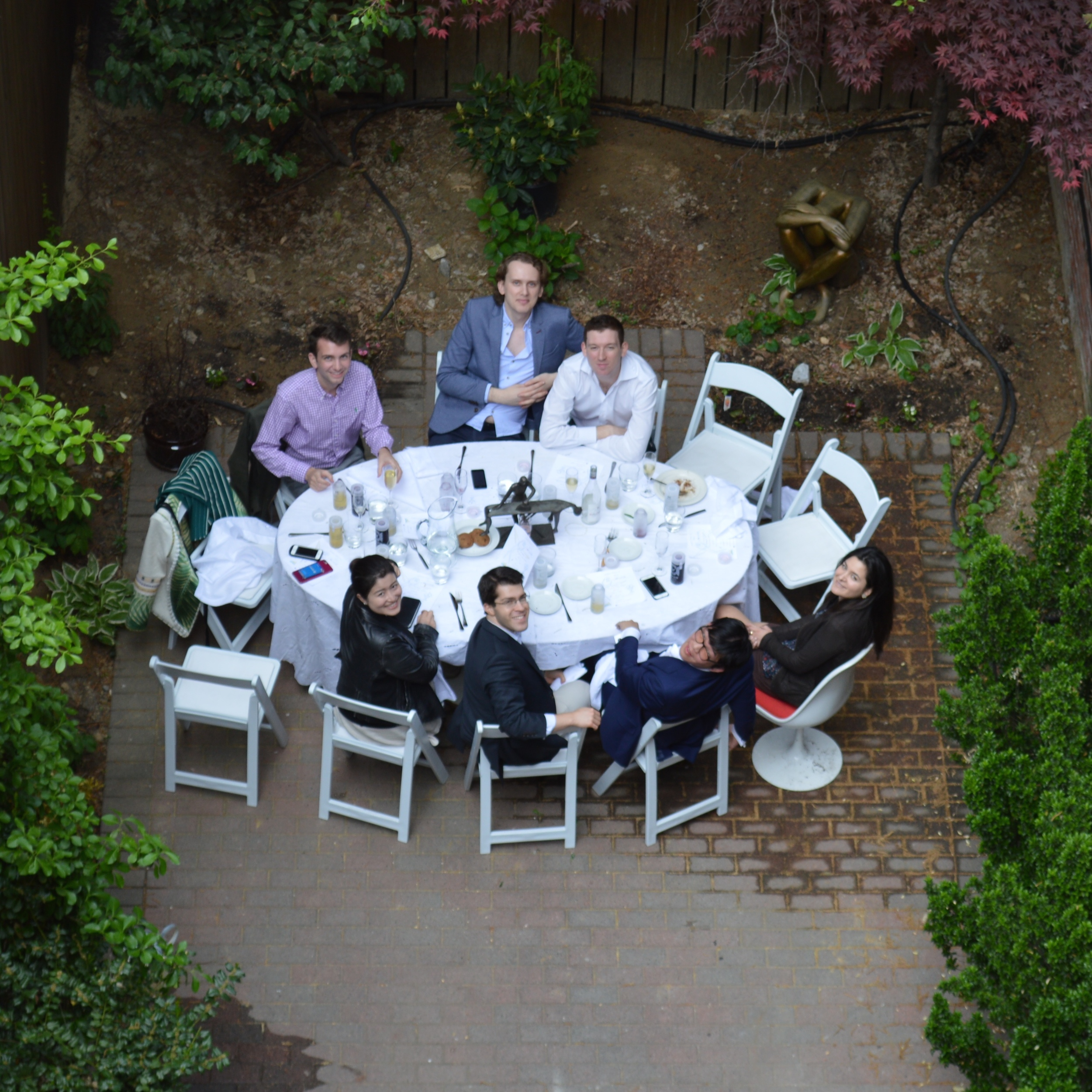 "The setting for lunch was the garden behind ""Kostabi World,"" Mark Kostabi's New York home and studio. A Kostabi sculpture featured as the table's centerpiece to foster conversation during the meal. Another sculpture was behind the table."