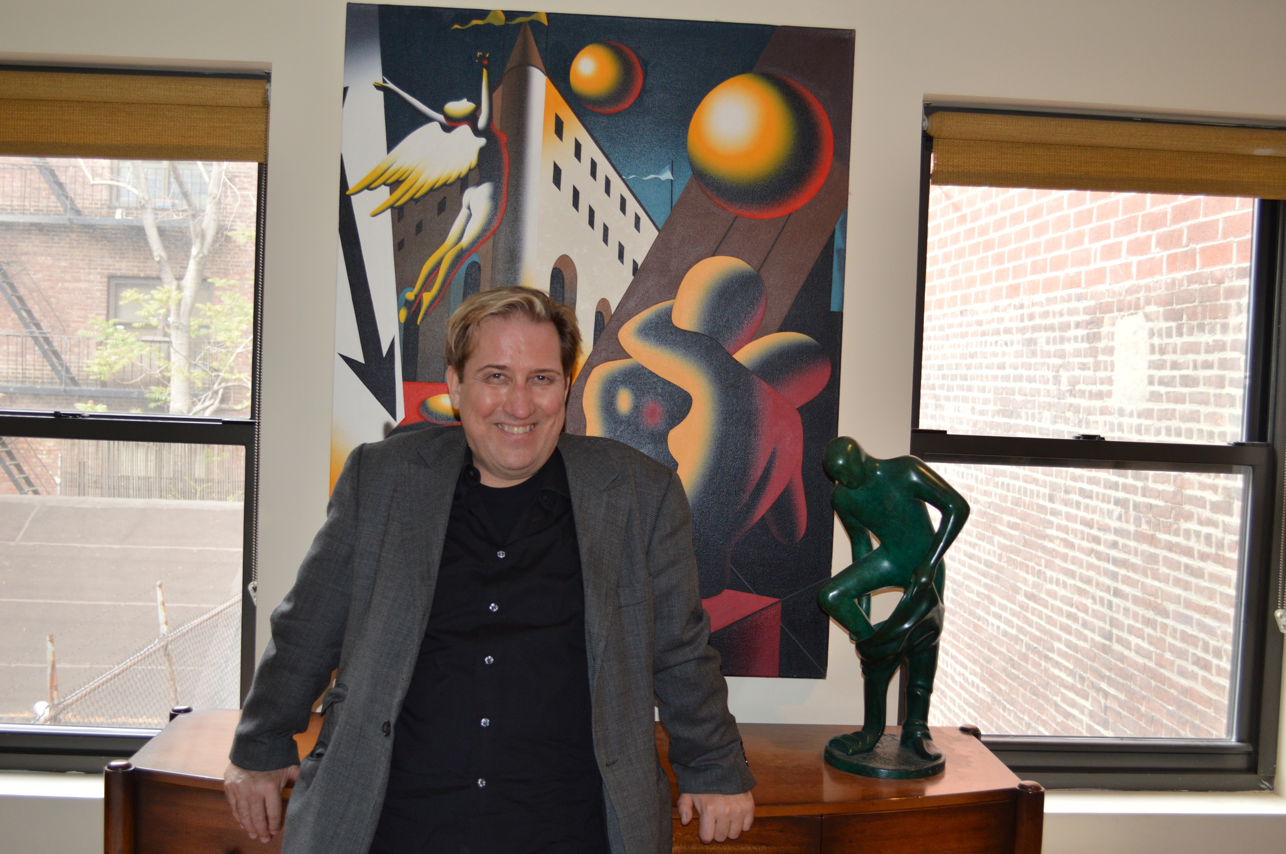 Mark Kostabi posing in front of his work.