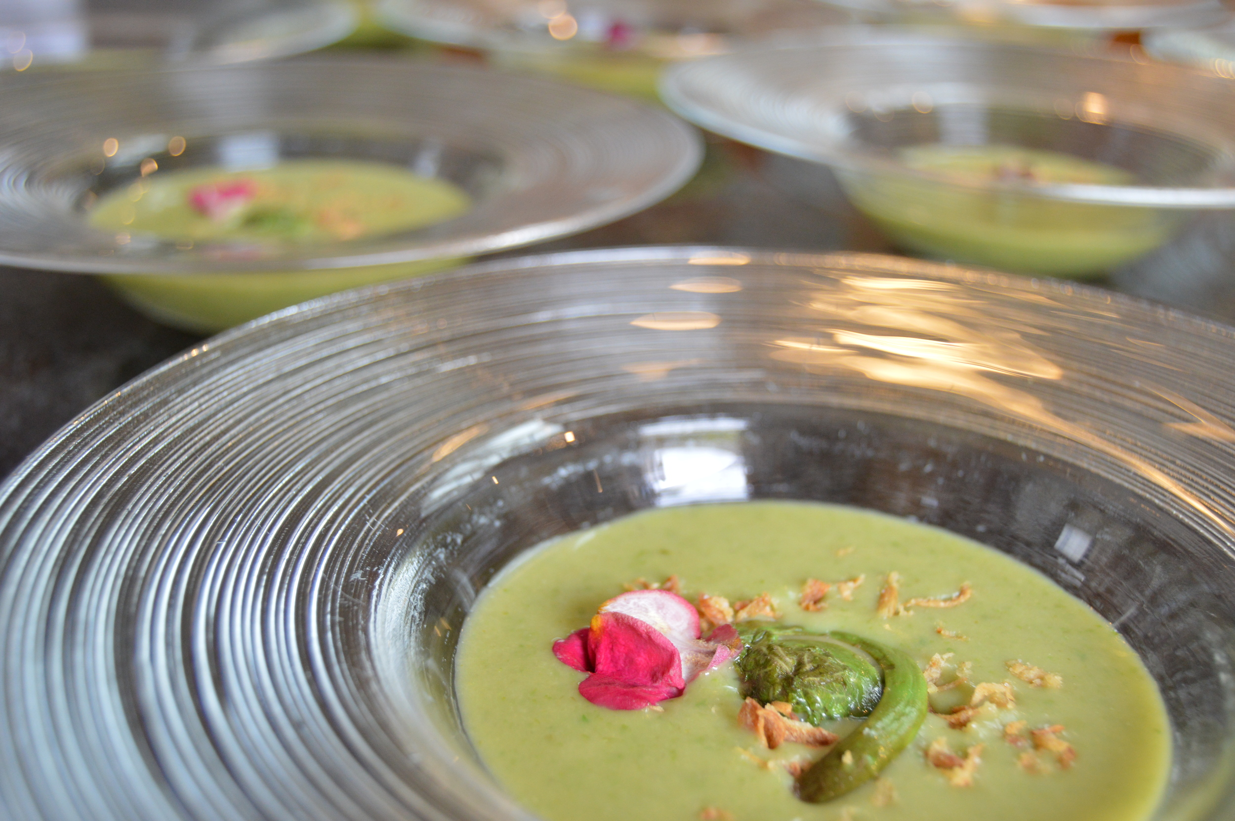 Chilled Asparagus Soup garnished with Crispy Onions, Fiddlehead Ferns, and Edible Flower Petals