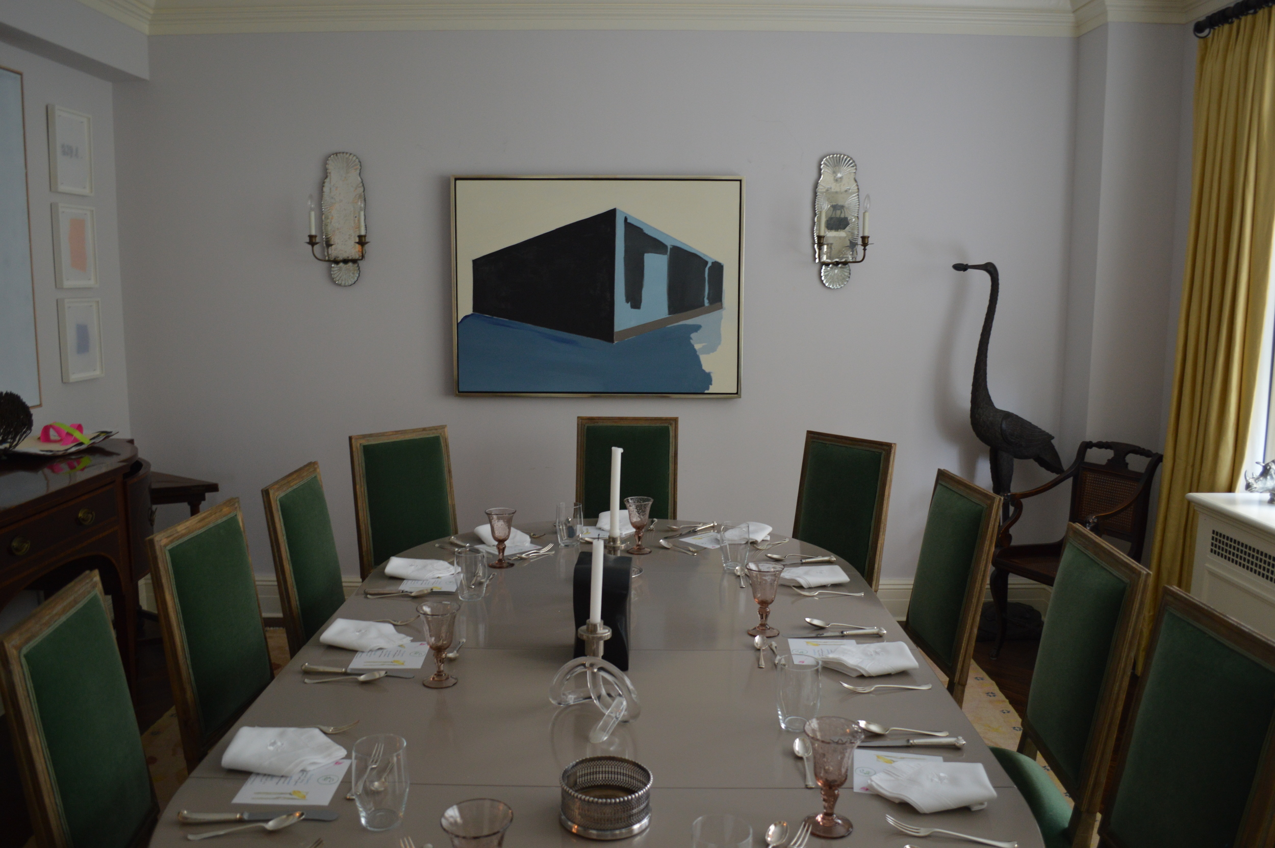 The table set for 12 members and guests, surrounded by painting and sculpture.