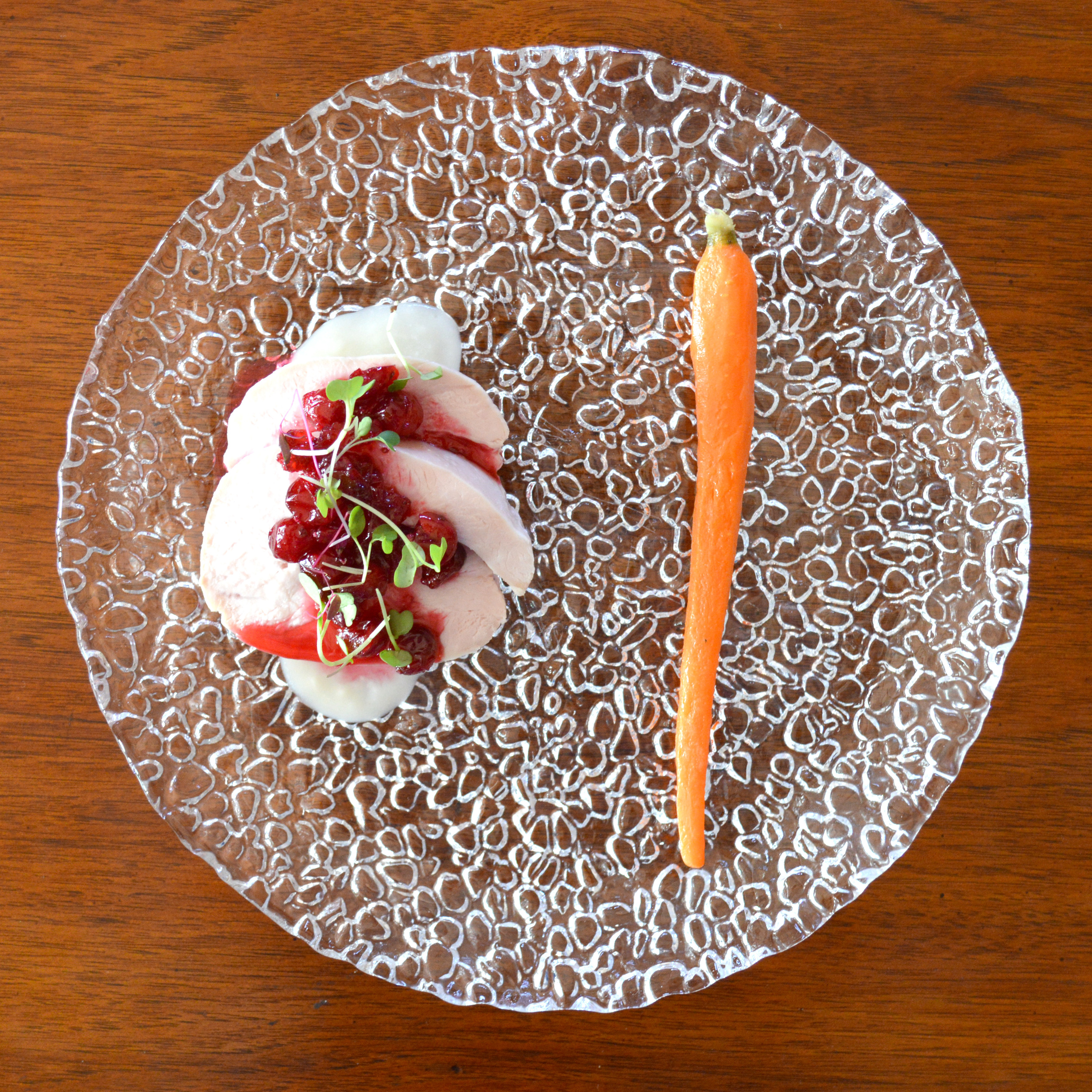 Sous-vide truffle turkey over gravy, under cranberry sauce and microgreens. Accompanied by a carrot.