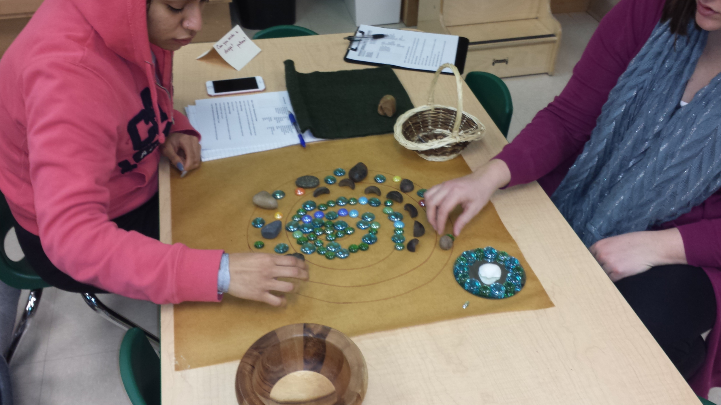 Early Childhood Educators engaged in a nature play station, designing with natural materials.