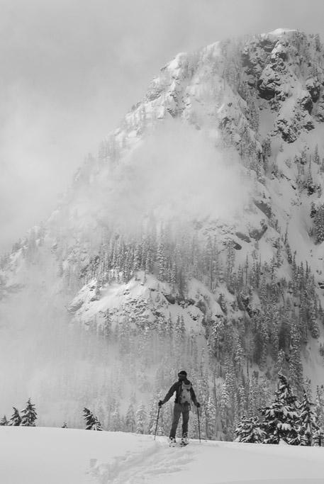 A backcountry skier surveys Guye Peak at Snoqualmie Pass, Central Cascades, Washington