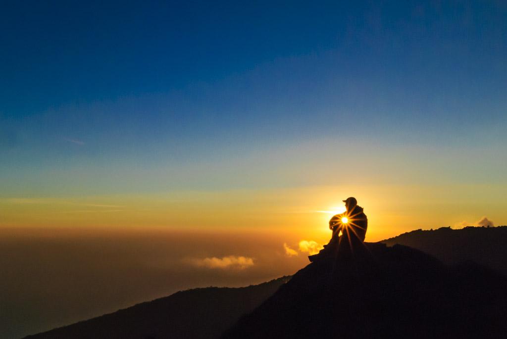 A climber watches sunset on Kilimanjaro, Tanzania