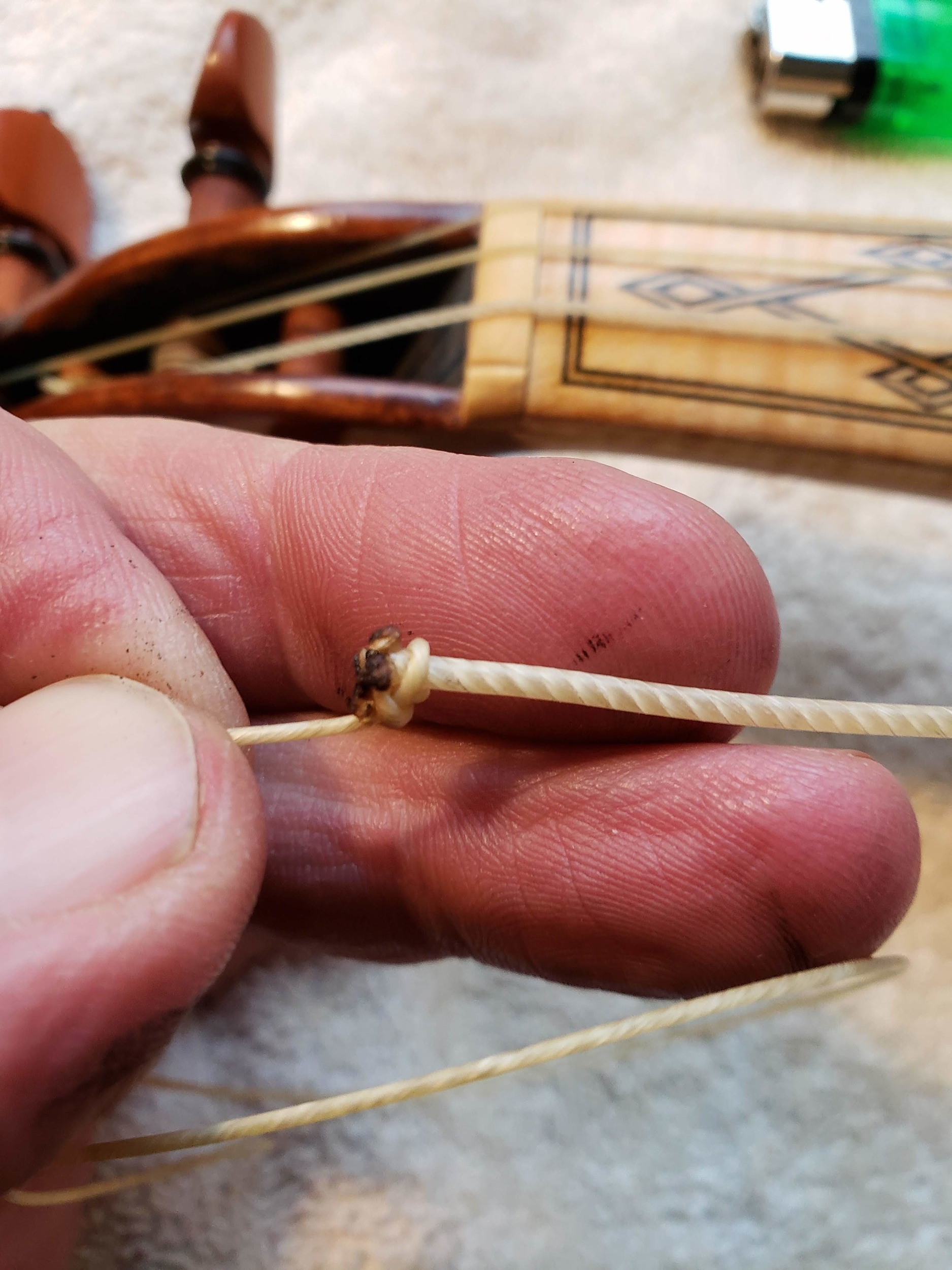 Step 12 - Pull the slip-knot tight and snug against the mushroomed end of the playing srtring.