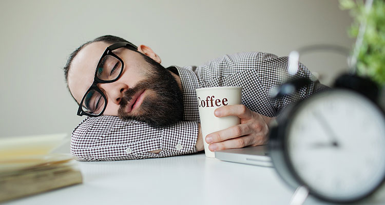 man-taking-a-caffeine-nap-at-his-desk-with-coffee-mug-in-hand.jpg